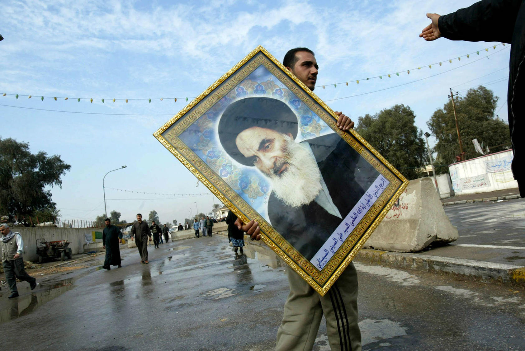 An Iraqi with a portrait of Grand Ayatollah Ali-Sistani, Iraq's most influential religious leader