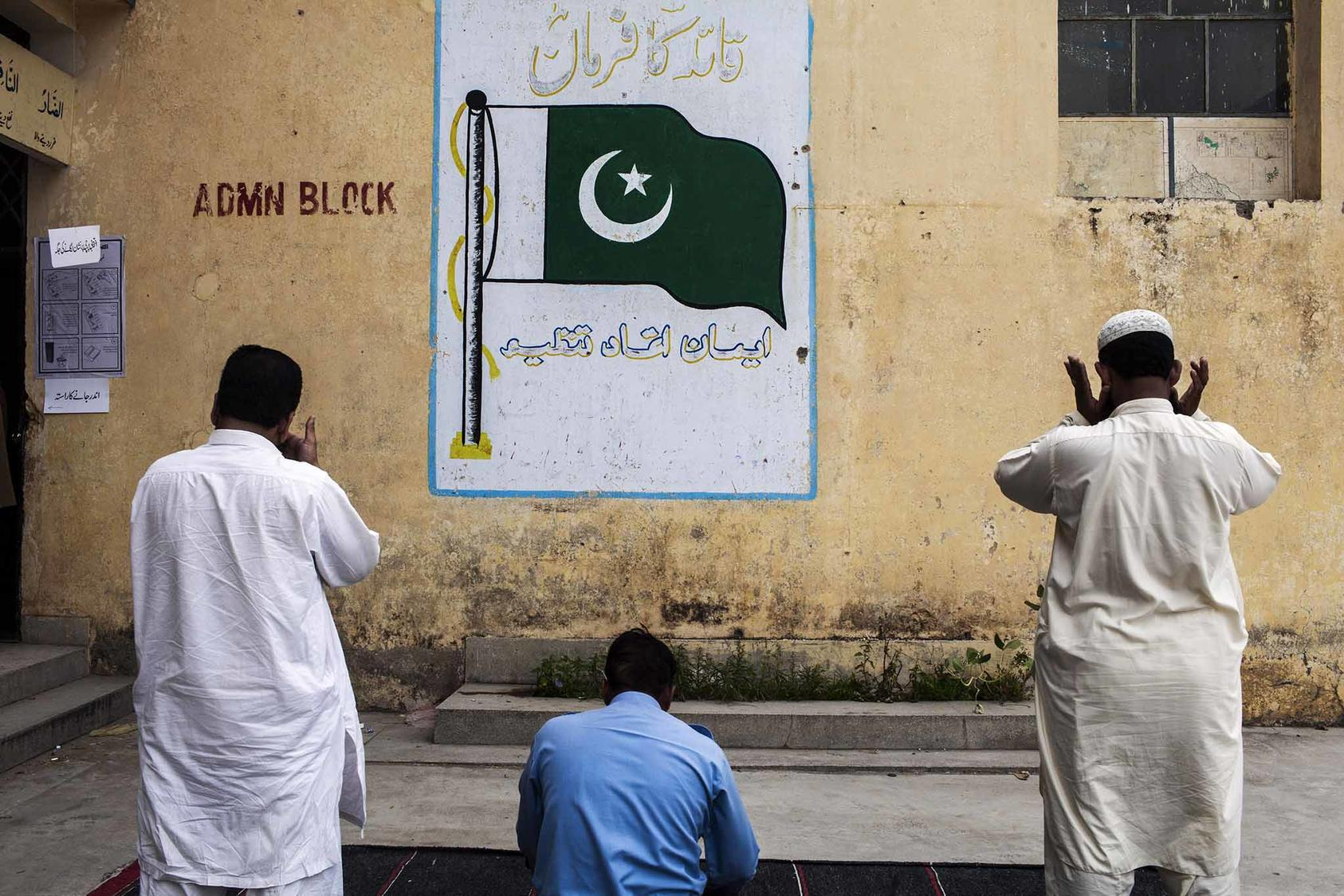 Men pray outside a polling station on Election Day in Islamabad, Pakistan in May 2013. (Diego Ibarra Sanchez/The New York Times)