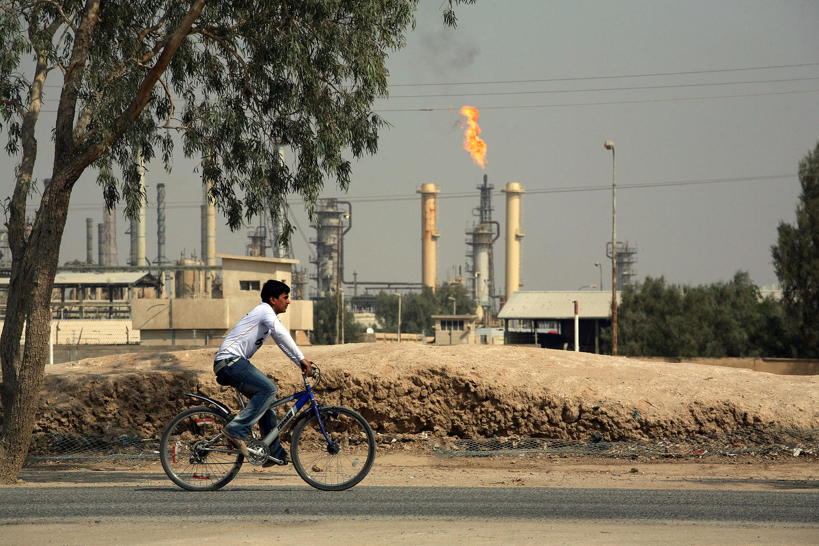 A bicyclist rides past a refinery near Basra, Iraq, on Oct. 27, 2009. (Joao Silva/The New York Times)