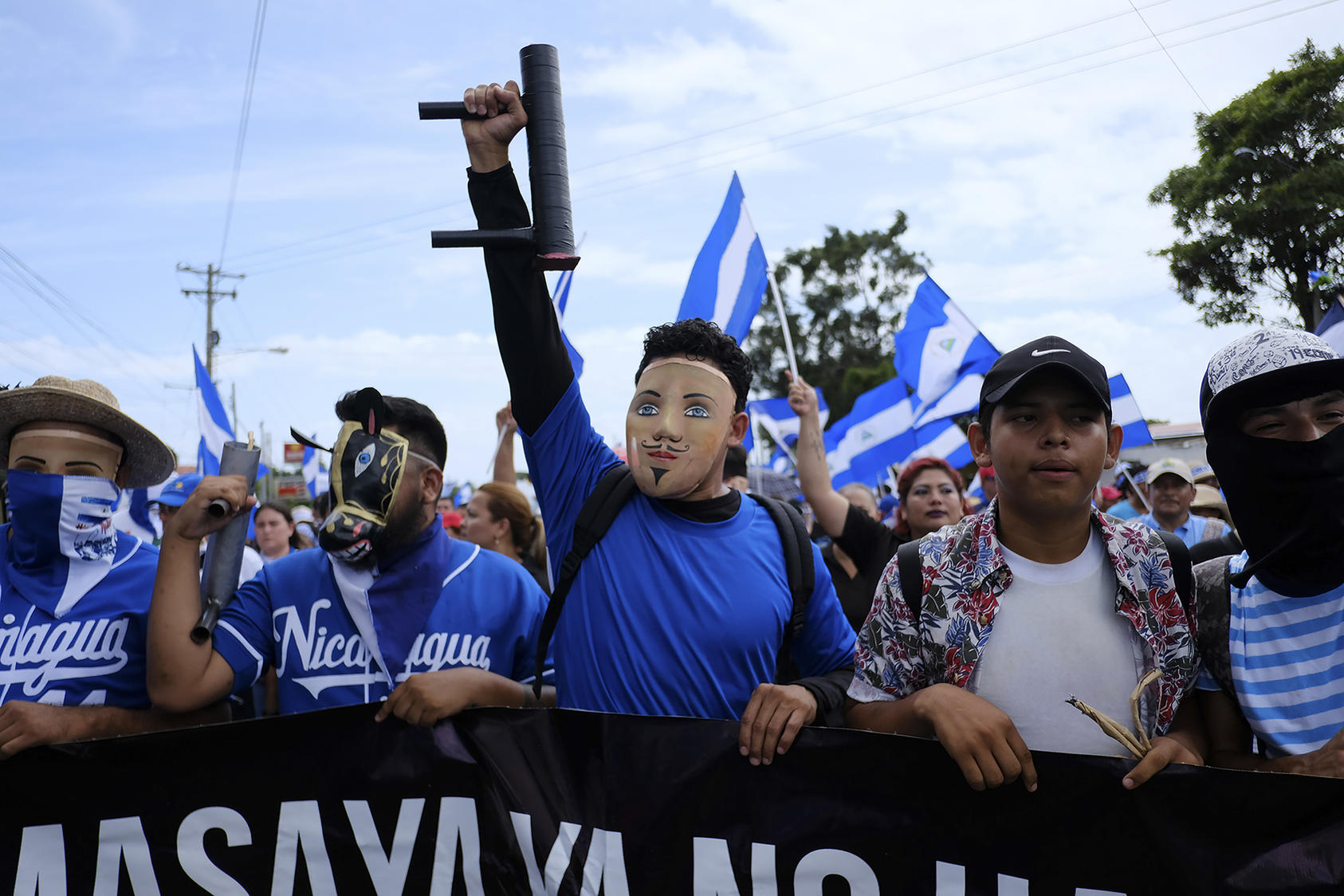 Protesters wearing folkloric masks and carrying crude, homemade mortars march through Managua, Nicaragua, July 12, 2018. (Brent McDonald/The New York Times)