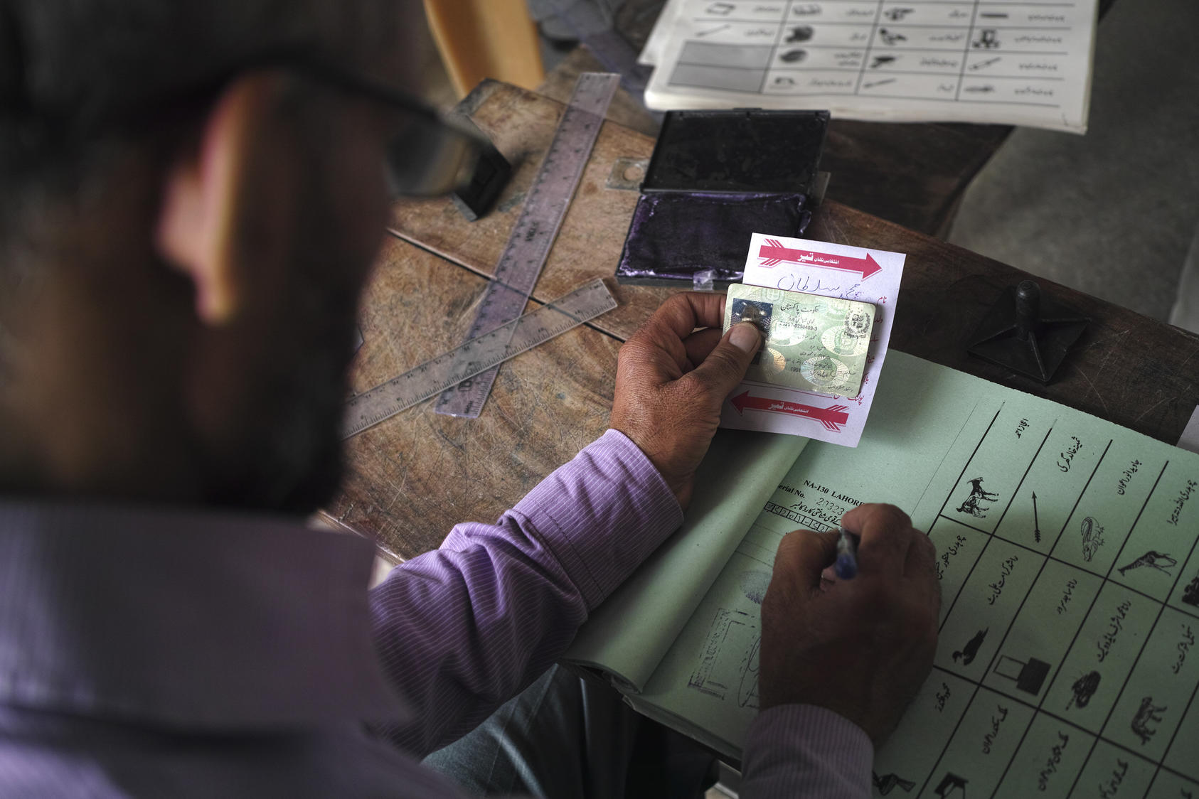 : Identification is checked at a polling station in Wagah, Pakistan (Tyler Hicks/The New York Times)