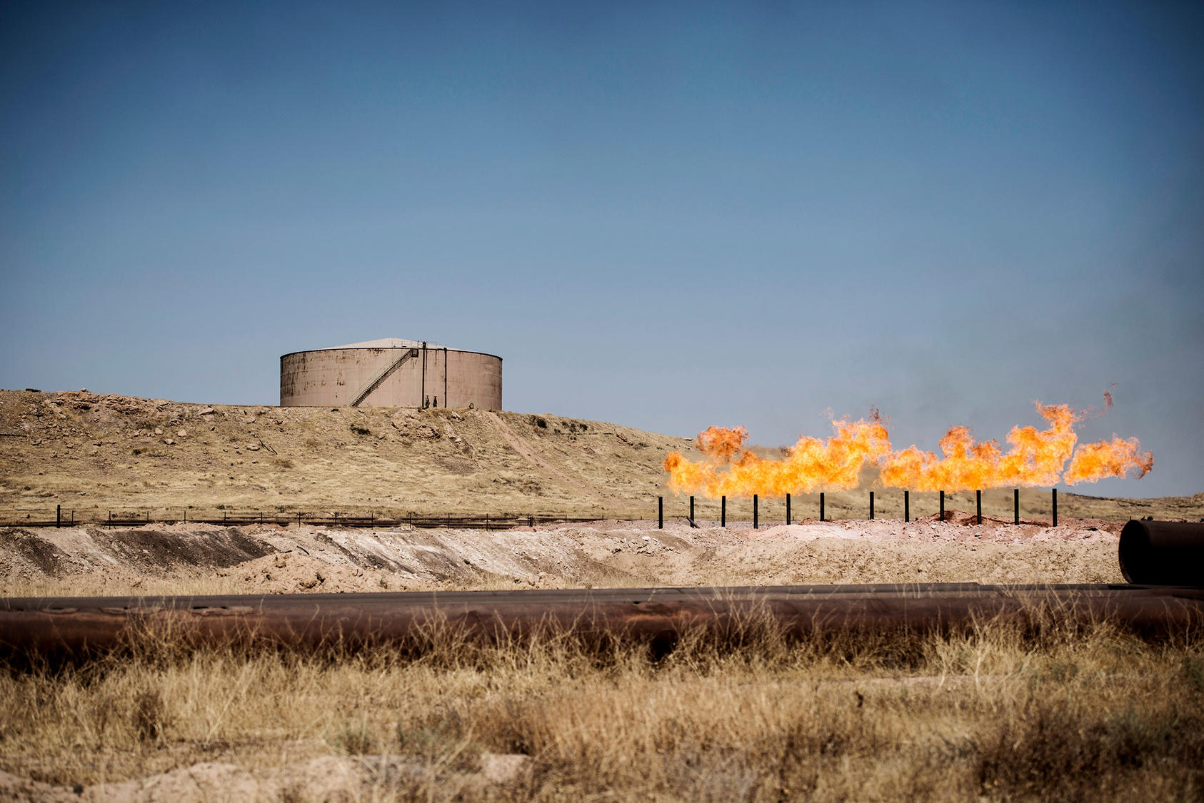 A gas flare burns near storage tanks in the oil fields near Kirkuk, Iraq