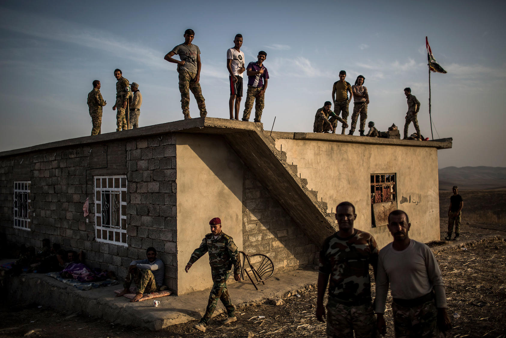 Fighters, who joined a militia to help liberate the city of Mosul from the Islamic State, wait at their base near the Mosul Dam near Karaj, Iraq, Oct. 18, 2016. (Bryan Denton/The New York Times)