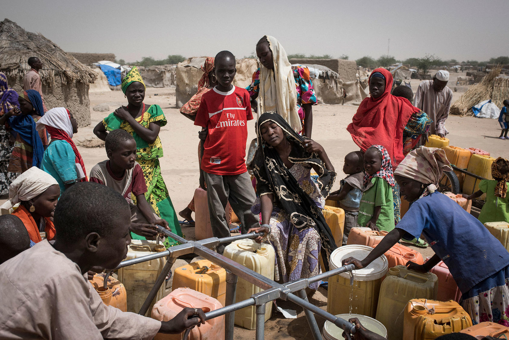 Nigerian refugees collect water from an International Rescue Committee point along National Route 1,