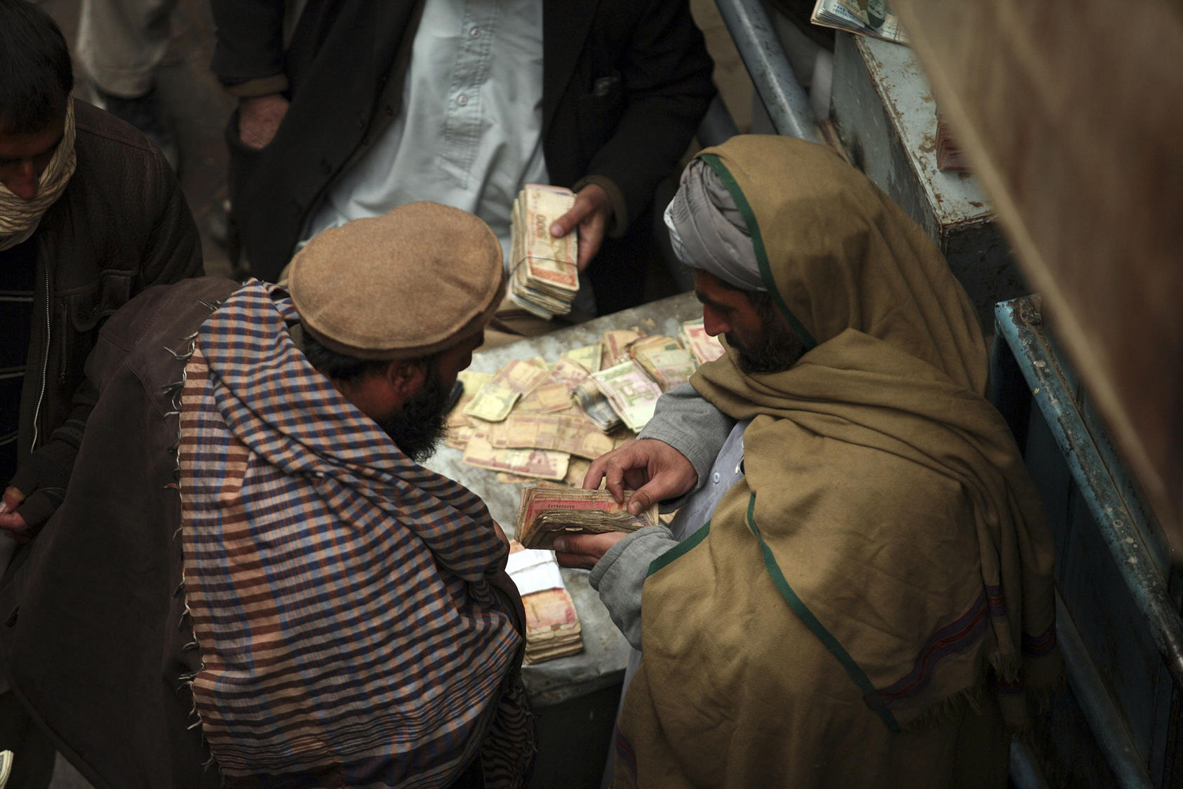 Men negotiate money exchanges at a market in Kabul. (Michael Kamber/The New York Times)