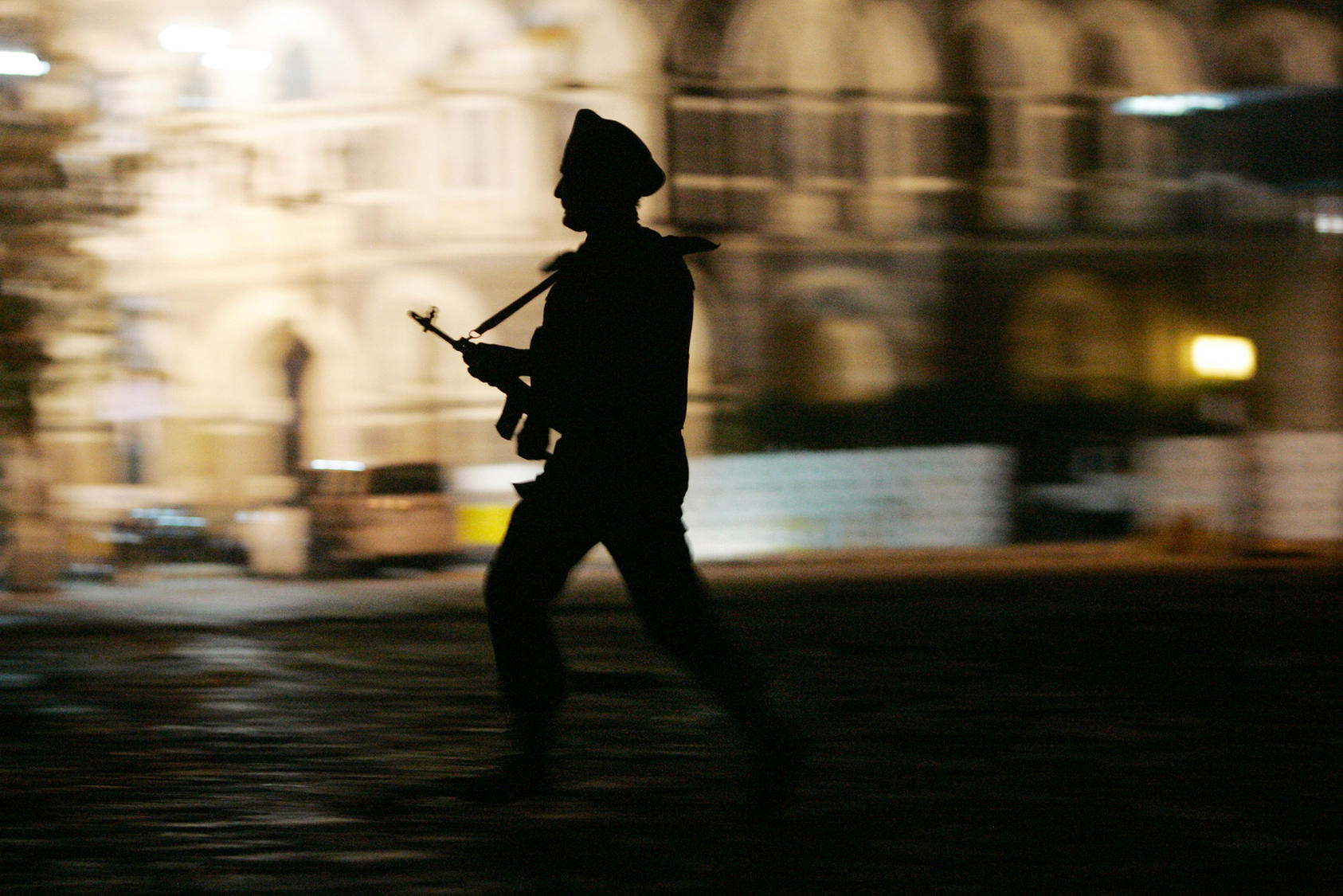 A soldier runs across the courtyard in front of the Taj Mahal Palace & Tower hotel in Mumbai, India, on Friday night, Nov. 28, 2008. (Amiran White/The New York Times)