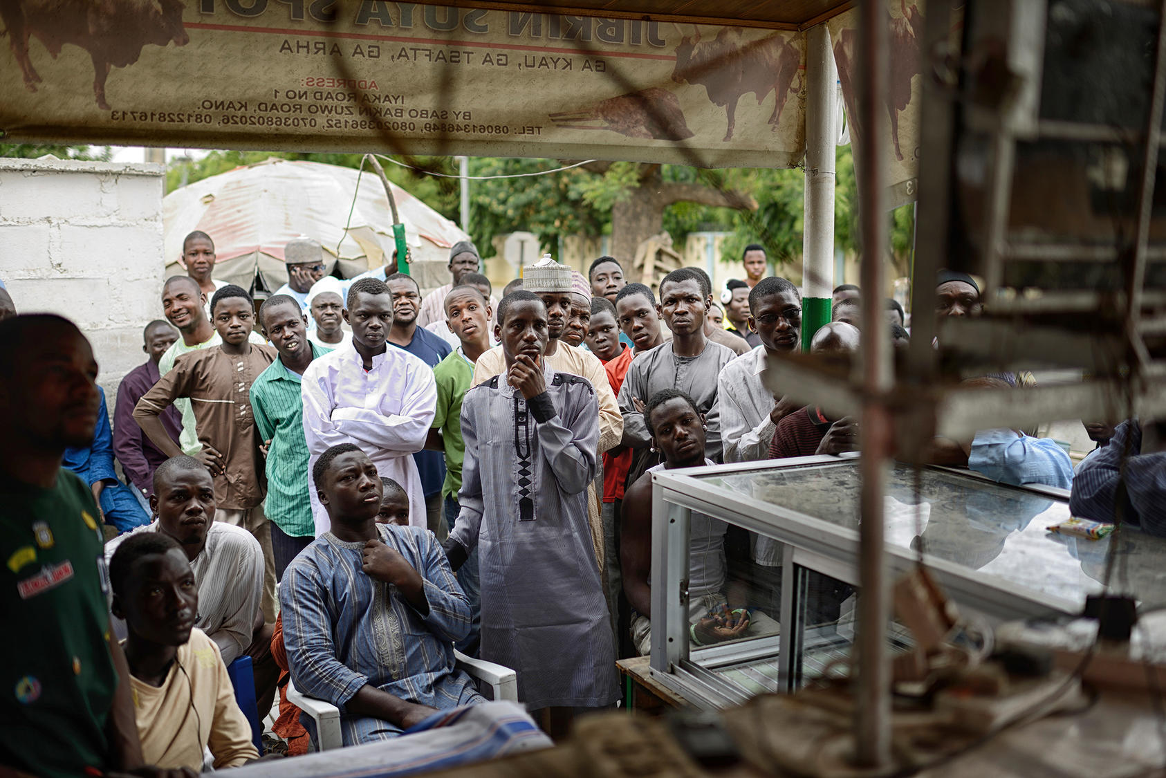 People gather and watch election coverage at a small market in Kano, northern Nigeria, March 31, 2015. (Samuel Aranda/The New York Times)