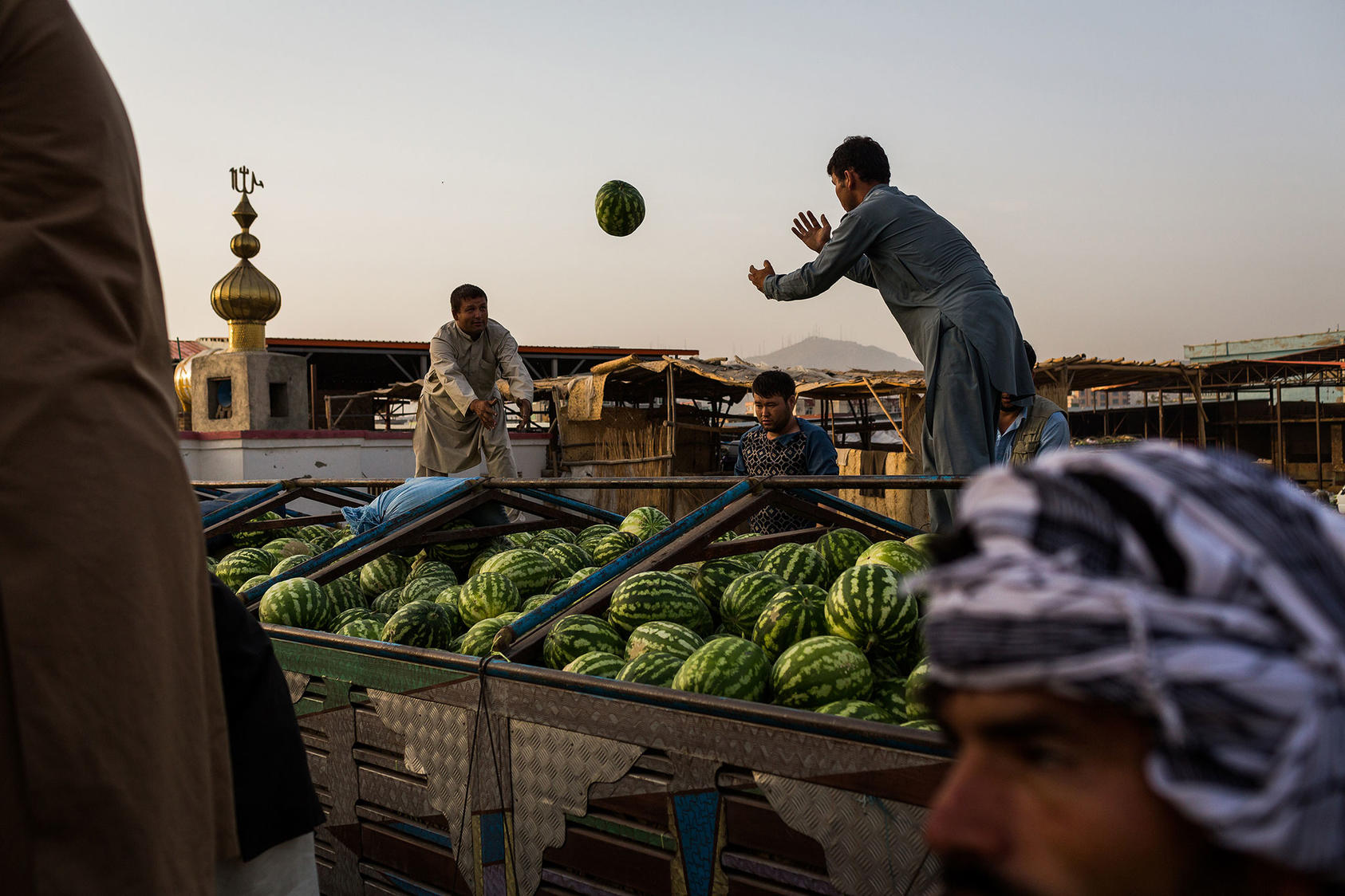Farmers unload melons at the melon market in Kabul, Aug. 8, 2017. As bountiful as the fruit is this season, the Taliban and militias defending the government against it have taken a toll on farmers and traders. (Jim Huylebroek/The New York Times)