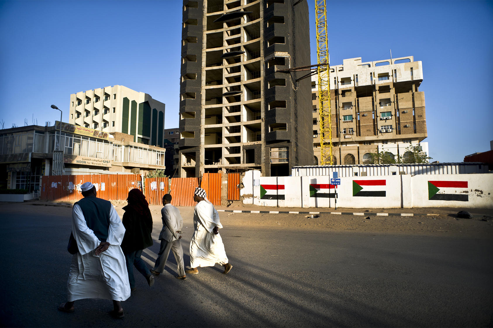 Locals walk pass a paused development project in Khartoum, Sudan, Jan. 26 2012. (Sven Torfinn/The New York Times)