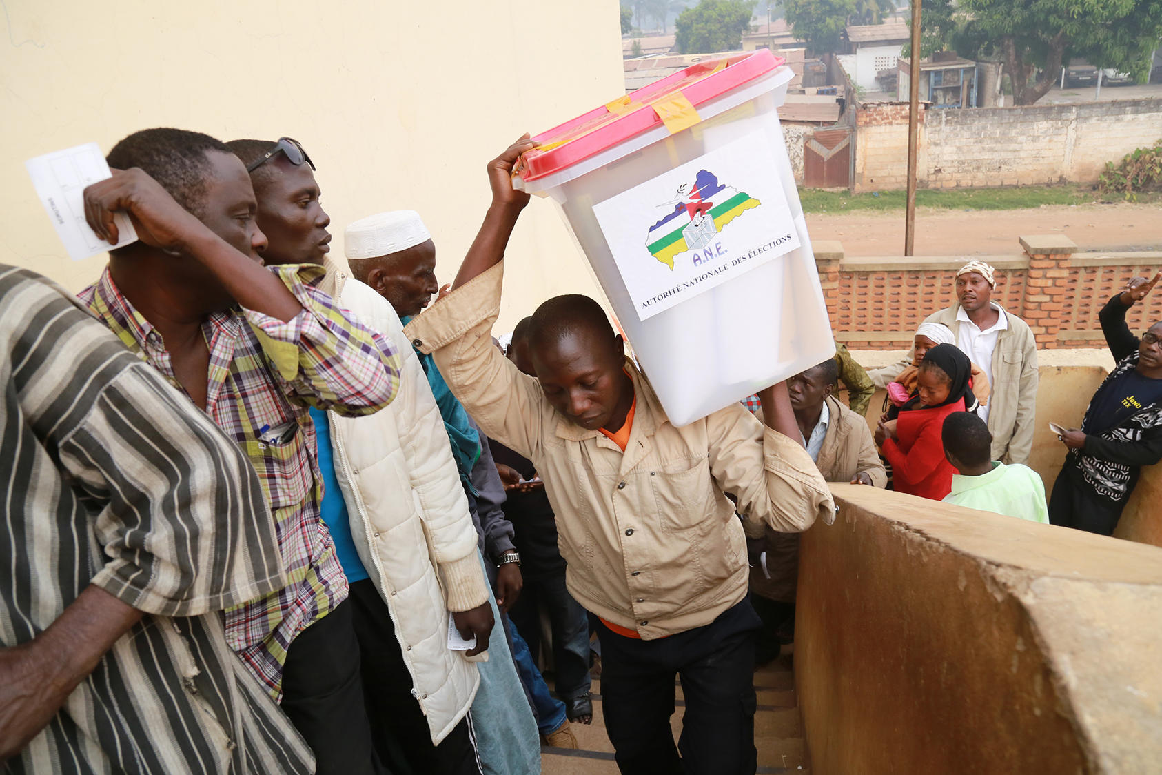 An electoral officer carries election materials into a polling station in Bangui in 2015 as queuing voters look on. (UN Photo/Nektarios Markogiannis)