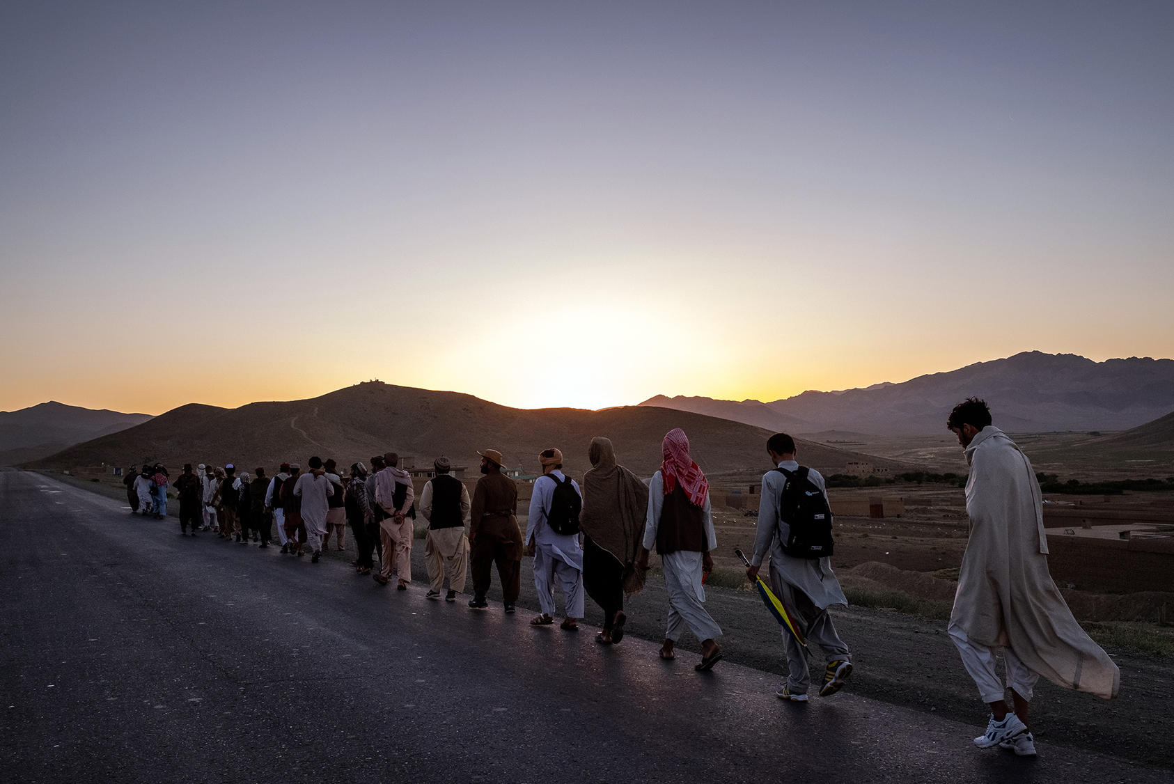 Dozens of men march for peace through southern Afghanistan, near Ghazni, on June 12, 2018. Talks between the Americans and the Taliban have many Afghans caught up in the hope of an unprecedented moment. (Jim Huylebroek/The New York Times)