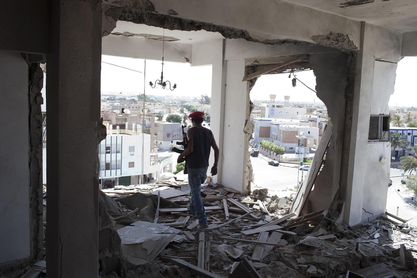 An armed resident of Tripoli, surveys damage from fighting in 2011. This month's offensive has displaced thousands and risks a new battle for the capital city. (Tyler Hicks/The New York Times)