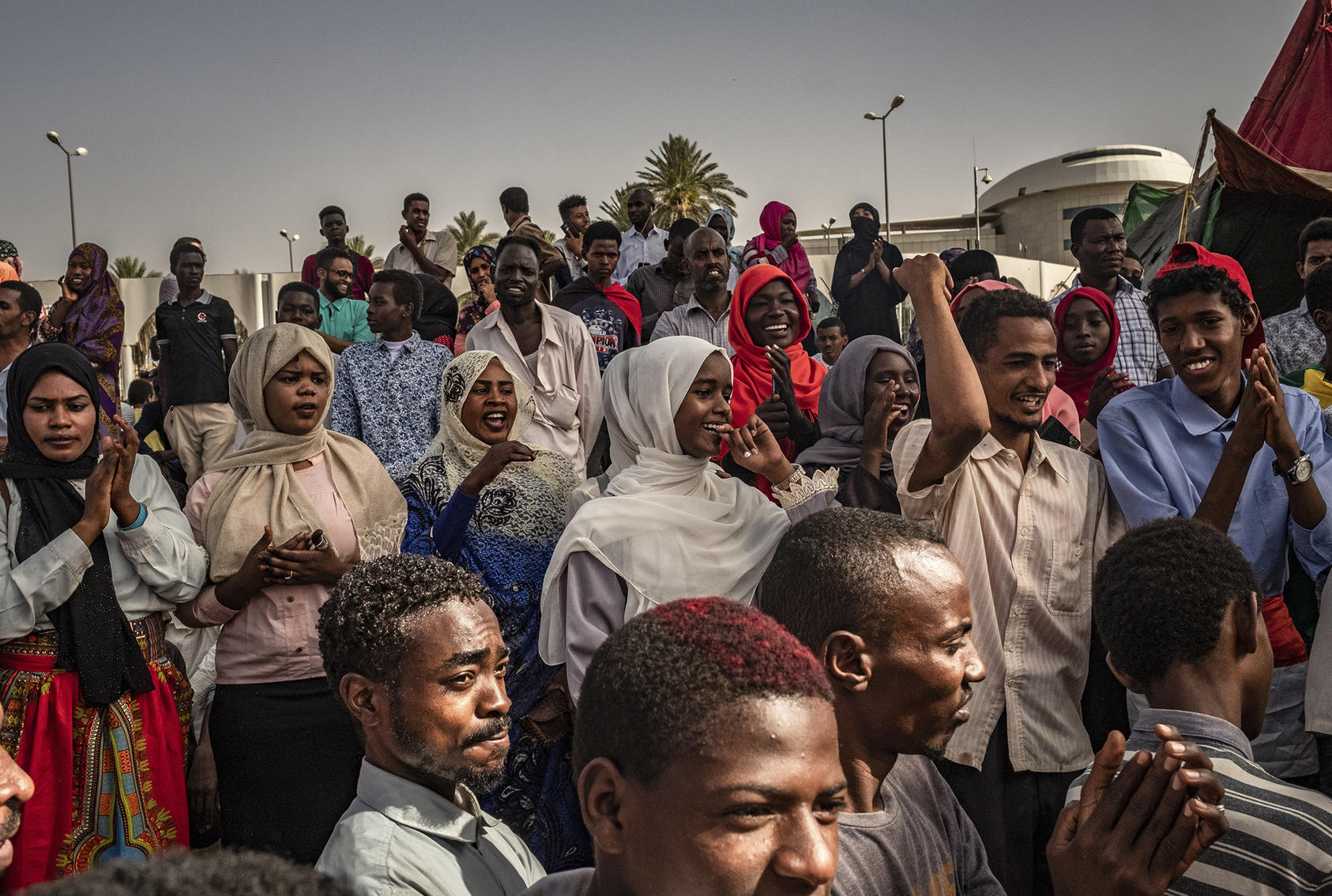 Men and women listen to music, sing and chant during a sit-in at the military headquarters in Khartoum, Sudan, April 27, 2019. (Bryan Denton/The New York Times)