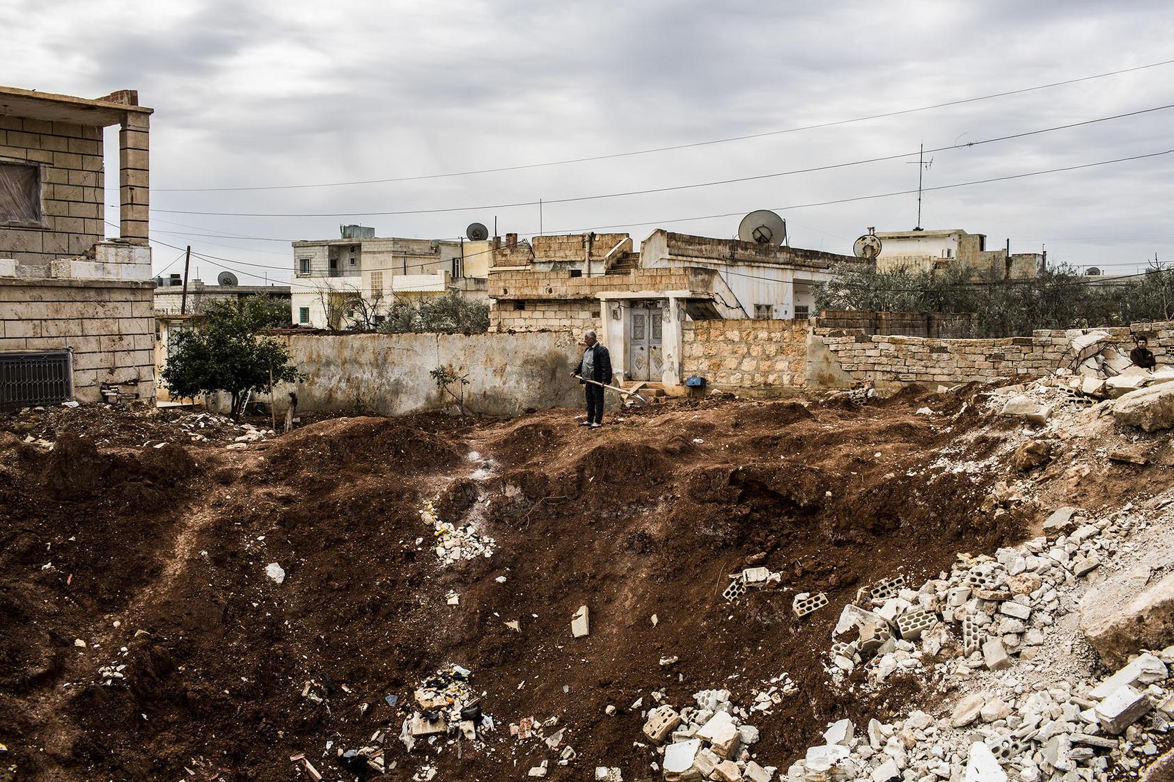A resident of Syria's Idlib province surveys a crater from a missile strike in 2013. As the province faces a new offensive, its nascent women's movement has had to close some of its education centers for women and girls. (Bryan Denton/The New York Times)