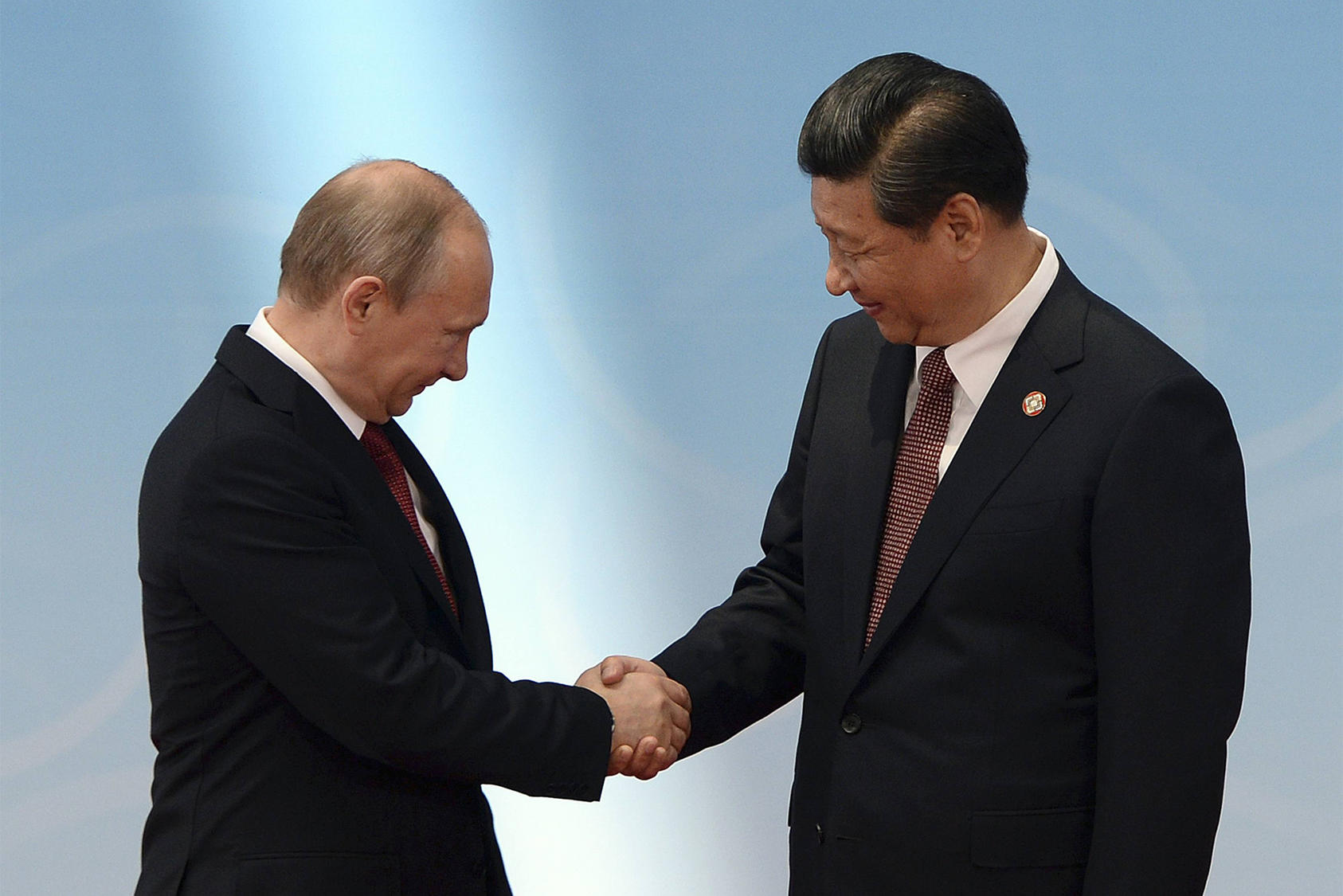 Russian President Vladimir Putin shakes hands with Chinese President Xi Jinping before a summit in Shanghai, May 21, 2014. (Mark Ralston/Pool via The New York Times)