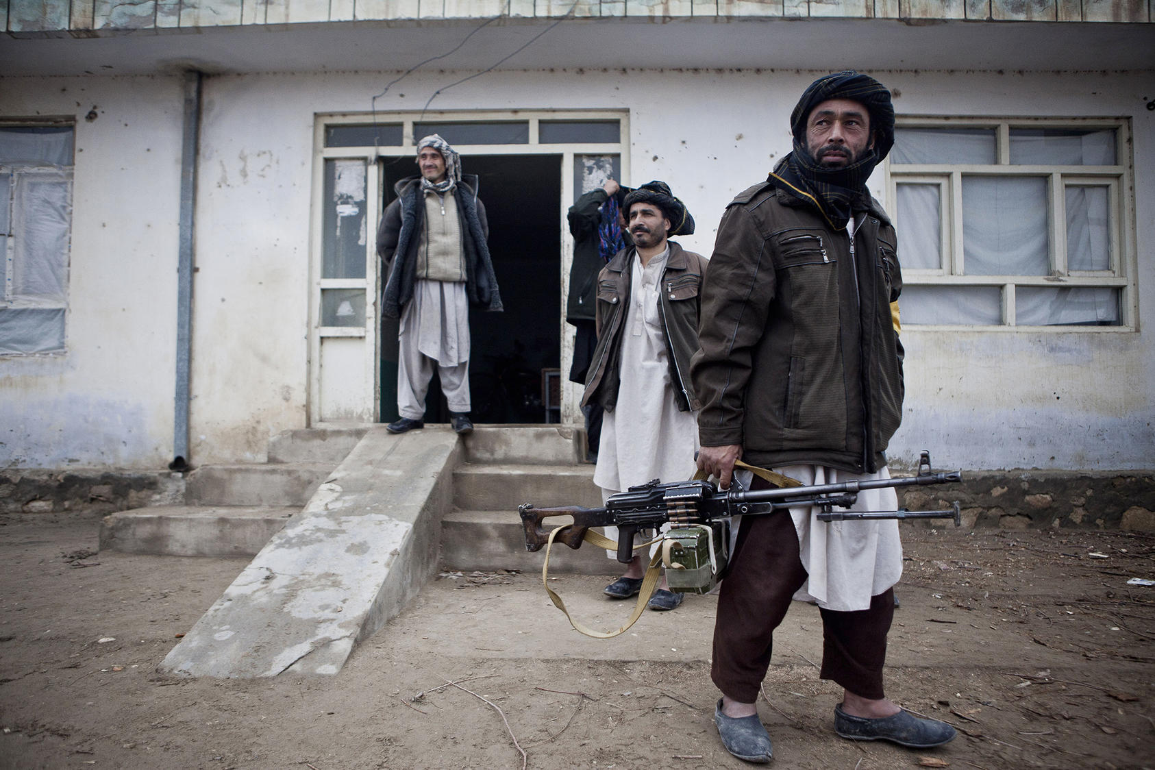 Men from one of Afghanistan's many militia forces carry a machine gun on patrol in Balkh province. Years of war have made guns and combativeness more central to Afghan men's ideas of masculinity—a hurdle to peacemaking. (Bryan Denton/The New York Times)
