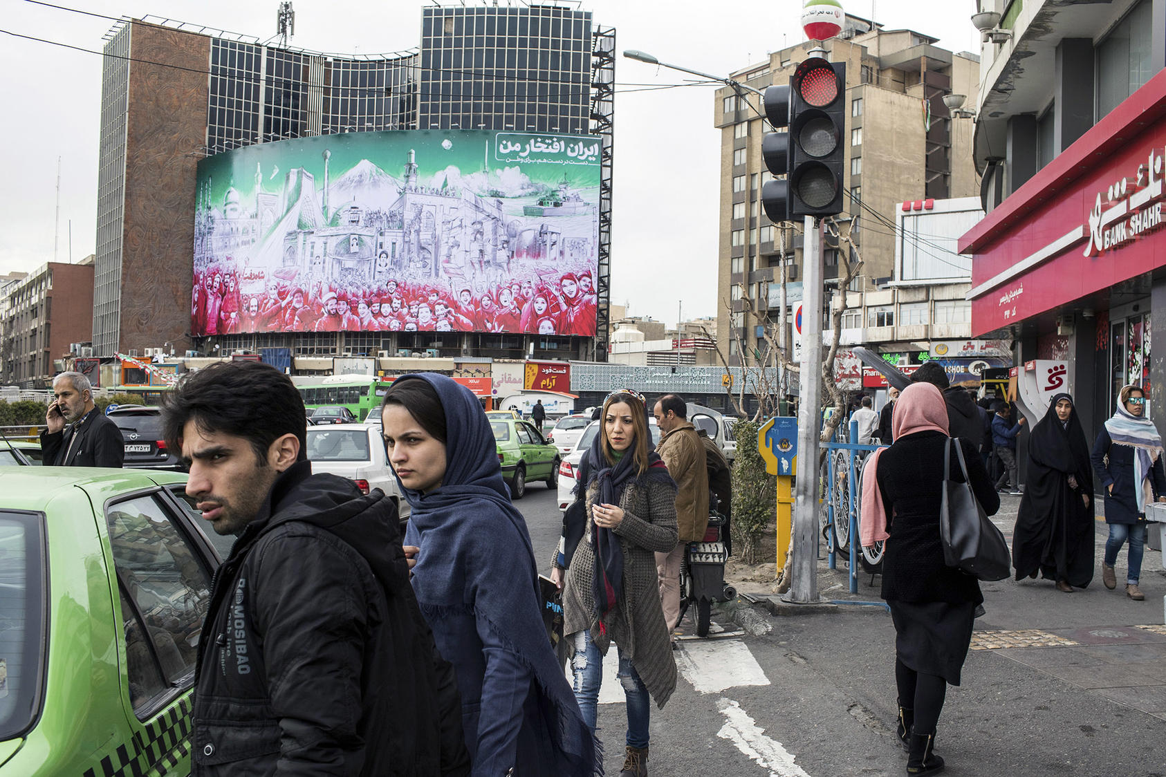 Iranians negotiate Tehran's traffic in February beneath a mural depicting the 1979 Islamic Revolution. U.S. sanctions, heightened this week, aim to pressure Iran's government into making broad foreign policy changes. (Arash Khamooshi/The New York Times)