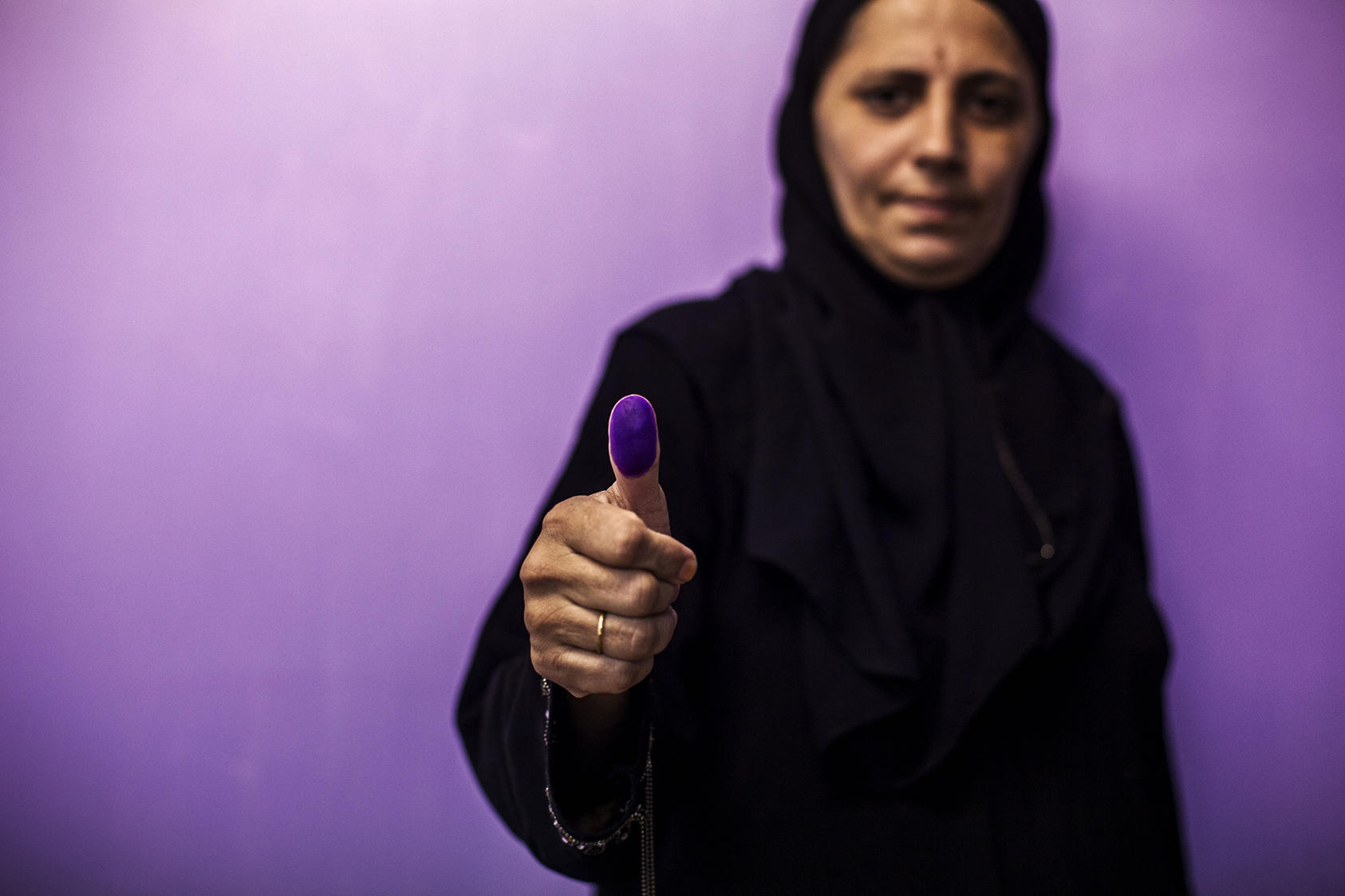 A woman shows her ink-covered thumb after casting her vote at a polling station during a repeat of the parliamentary election in Karachi, Pakistan, May 19, 2013. (Diego Ibarra Sanchez/The New York Times)