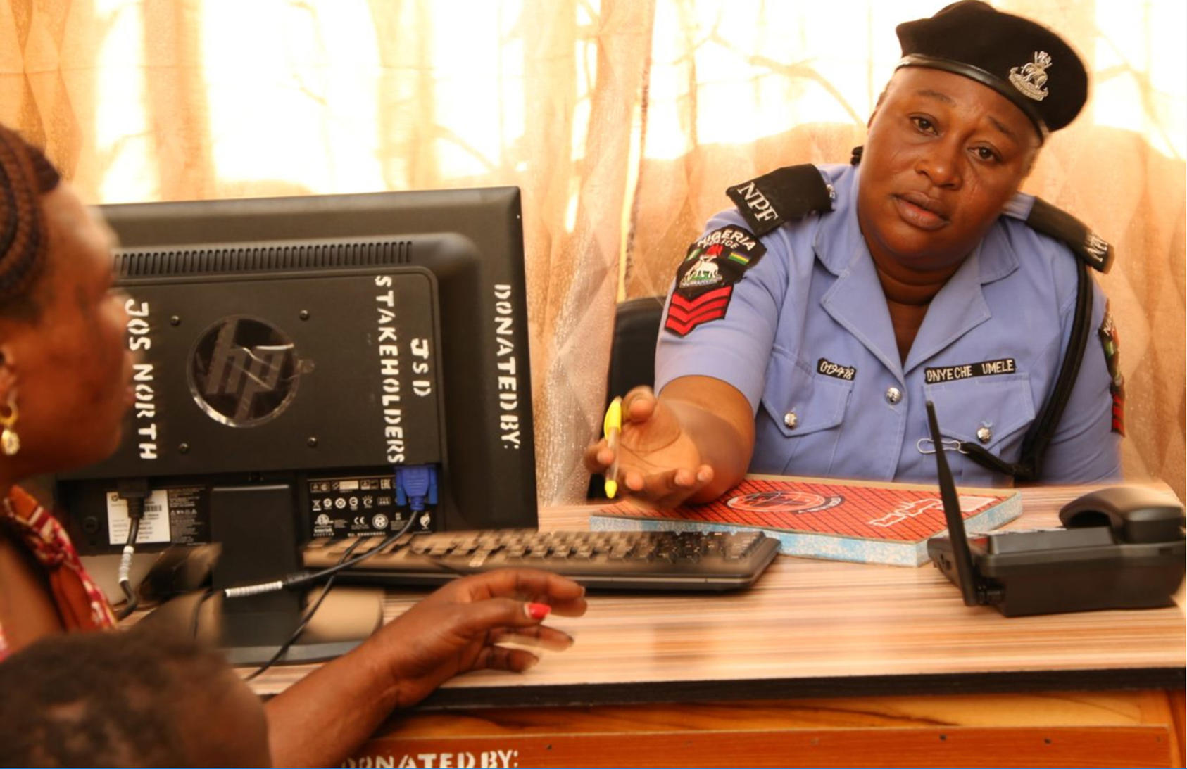 In Jos, officer Umele Onyeche hears a local woman's story at the city's first police unit dedicated to investigating sexual violence. Police and the community created the unit following a dialogue supported by USIP.