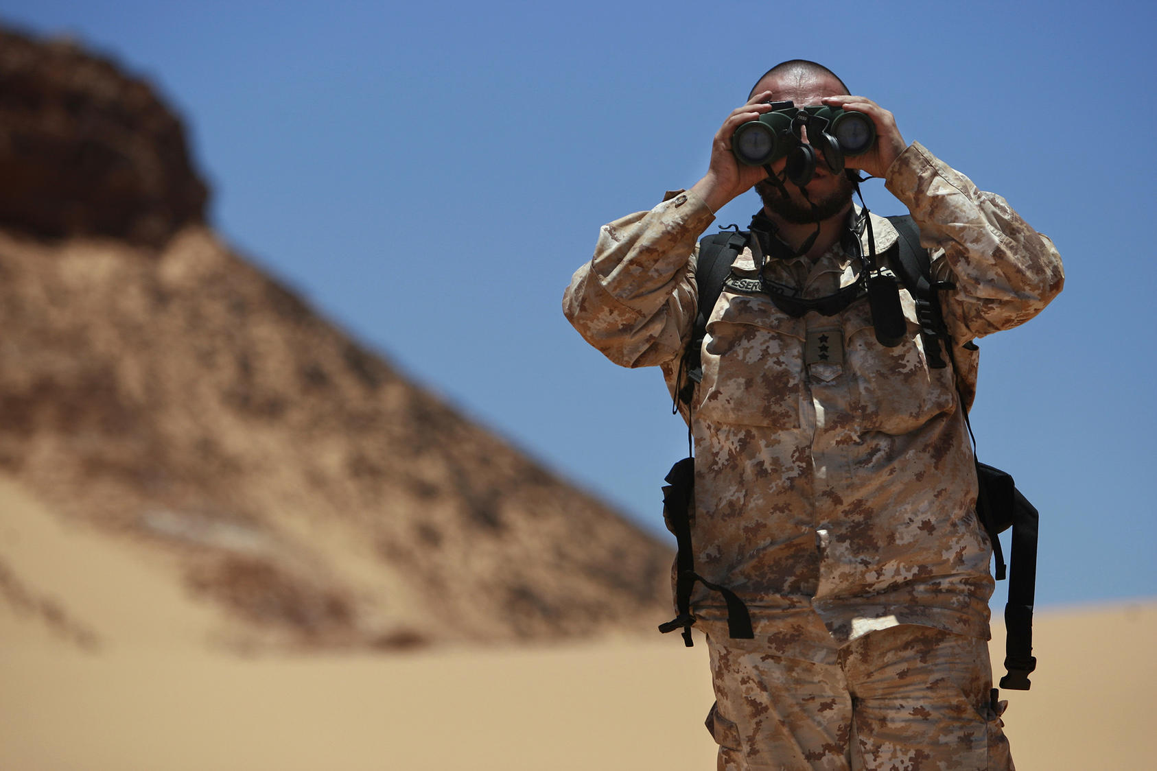 Antonio Achille, working with the Military Liaison Office of the U.N. Mission for the Referendum in Western Sahara, looks through binoculars during a cease-fire monitoring patrol in Oum Dreyga, Western Sahara. (United Nations Photo)