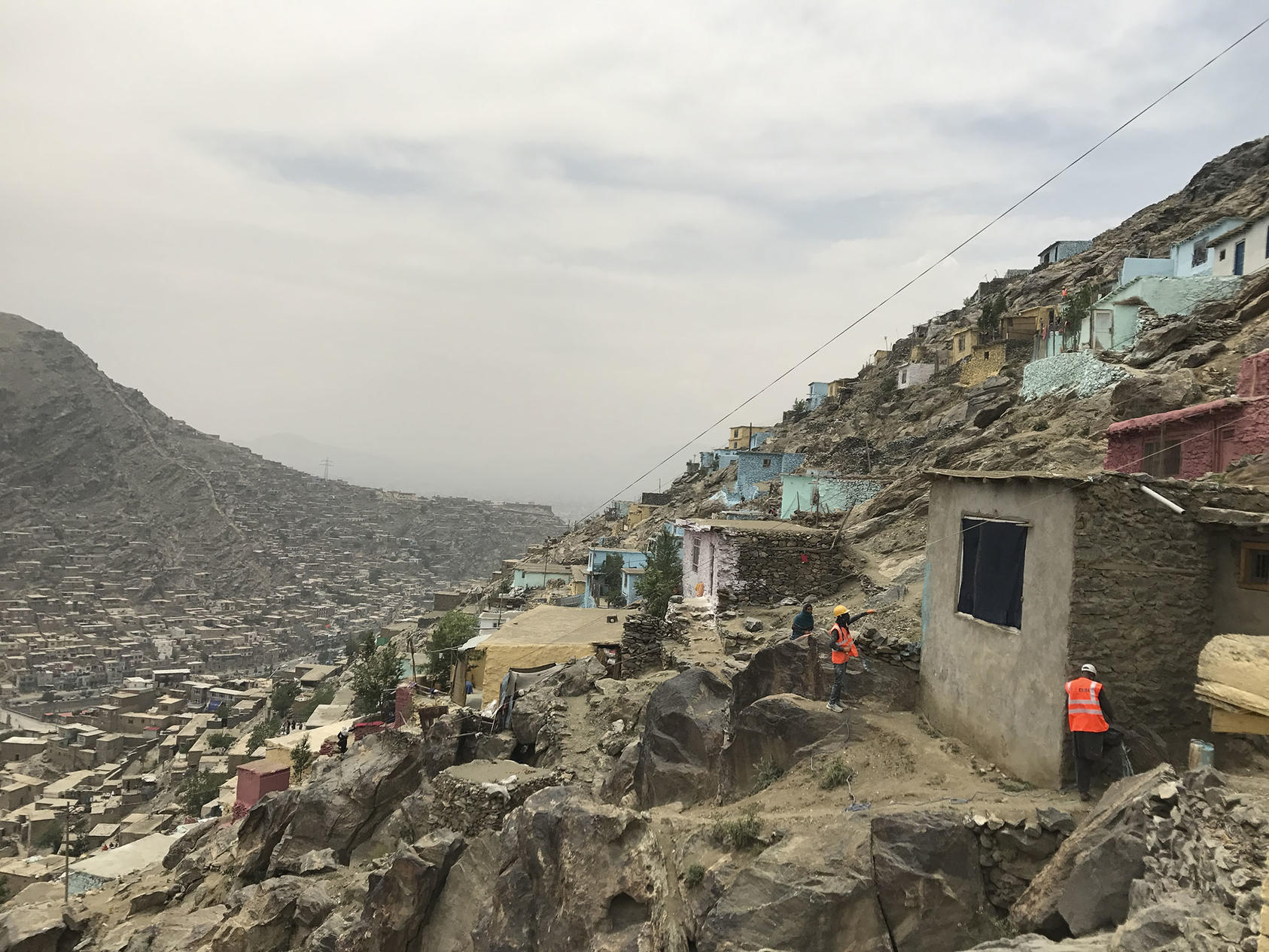 Slum neighborhoods climb Kabul's mountains, a result of the city's wartime population spike. Afghanistan will need a unified aid effort to rebuild its economy and fulfill any peace accord. (Fahim Abed/The New York Times)