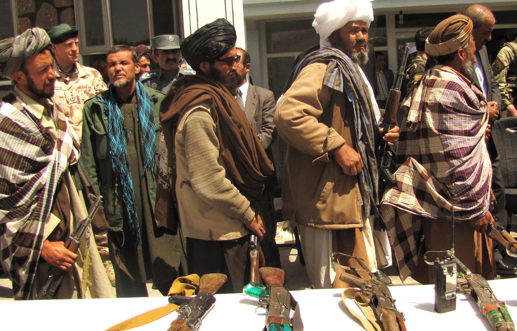 Former Taliban fighters line up to handover their rifles to the Afghan Government during a reintegration ceremony, May 2012. (Department of Defense/Lt. j. g. Joe Painter)