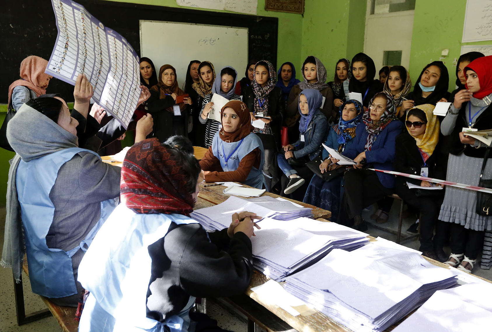 An electoral official examines a ballot in front of election observers during the 2018 parliamentary elections in Kabul, Oct. 21, 2018. (Fardin Waezi/UNAMA)