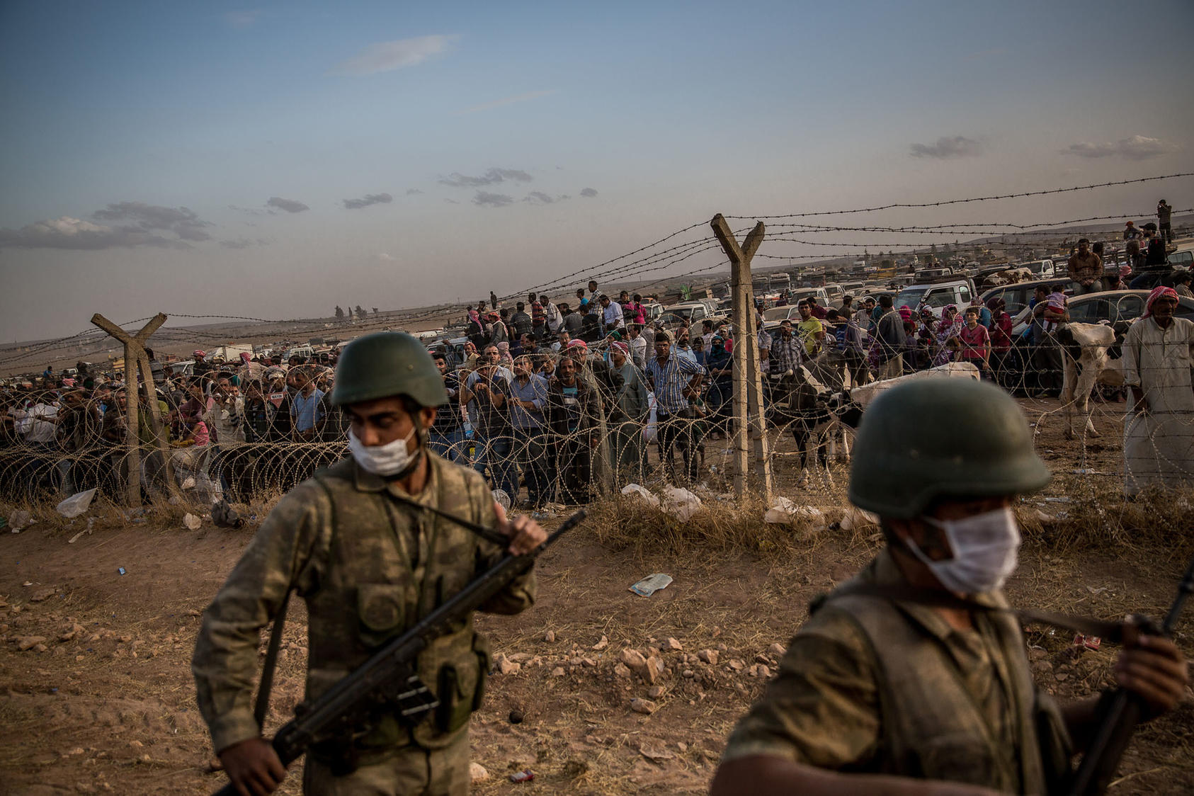 Turkish soldiers patrol a border fence as a crowd of Syrian Kurdish refugees watch and wait, at the Yumurtalik border crossing in Turkey Sept. 29, 2014. (Bryan Denton/The New York Times)