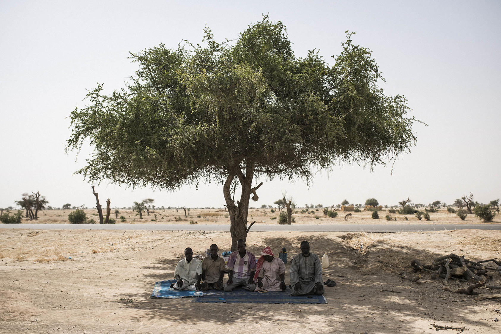 Nigerian men who fled their country's Boko Haram conflict seek shade to pray in neighboring Niger. Violence involving Boko Haram has uprooted most of the quarter-million Nigerians who have taken refuge in nearby states. (Adam Ferguson/The New York Times)
