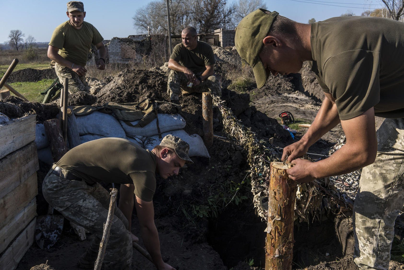 Ukrainian troops dig bunkers after withdrawing about 500 yards from the front line in the village of Stanytsia Luhanska. The pullback by both sides helped prepare for December 9 peace talks in the Russia-Ukraine war. (Brendan Hoffman/The New York Times)