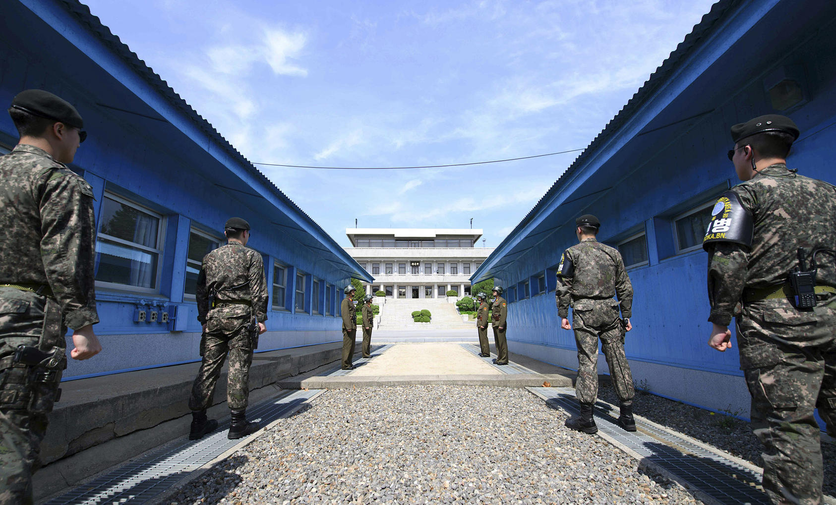 South Korean soldiers, front, and North Korean soldiers, rear, stand guard on either side of the Military Demarcation Line of the Demilitarized Zone dividing the two nations. (Korea Summit Press Pool via New York Times)