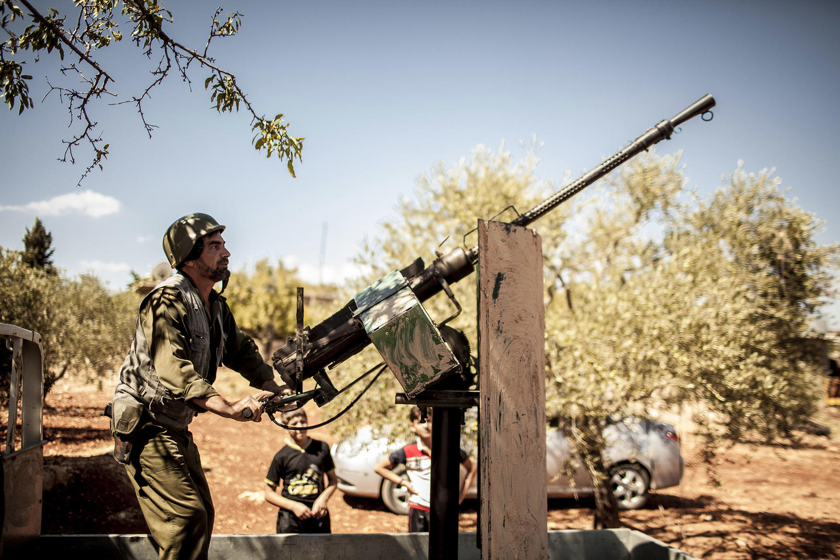 Hajj Abu Omar mounts an anti-aircraft gun in Idlib, Syria, Sept. 21, 2012. (Bryan Denton/The New York Times)