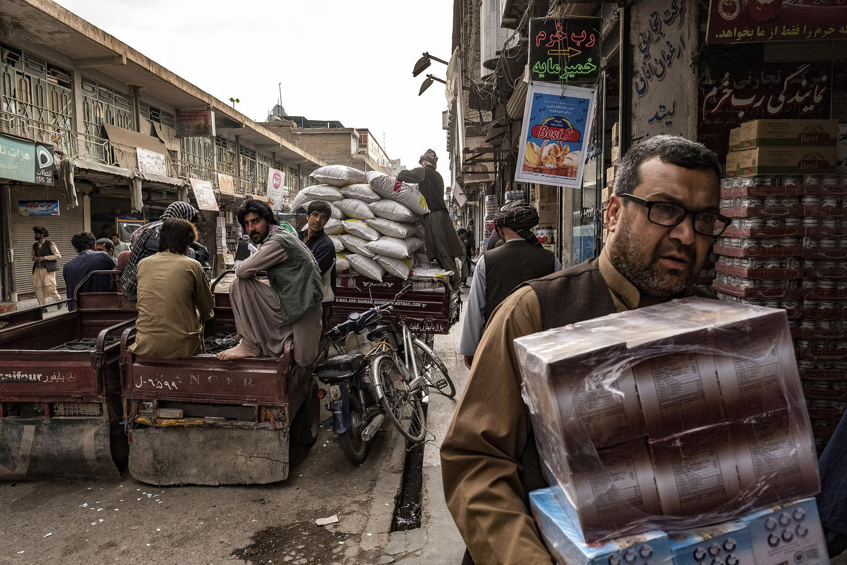 "Afghan laborers and merchants moved goods through a bazaar known for Iranian dry foodstuffs and other sundries in Herat, Afghanistan, which is sometimes called ""Little Iran,"" April 16, 2017. (Bryan Denton/The New York Times)"