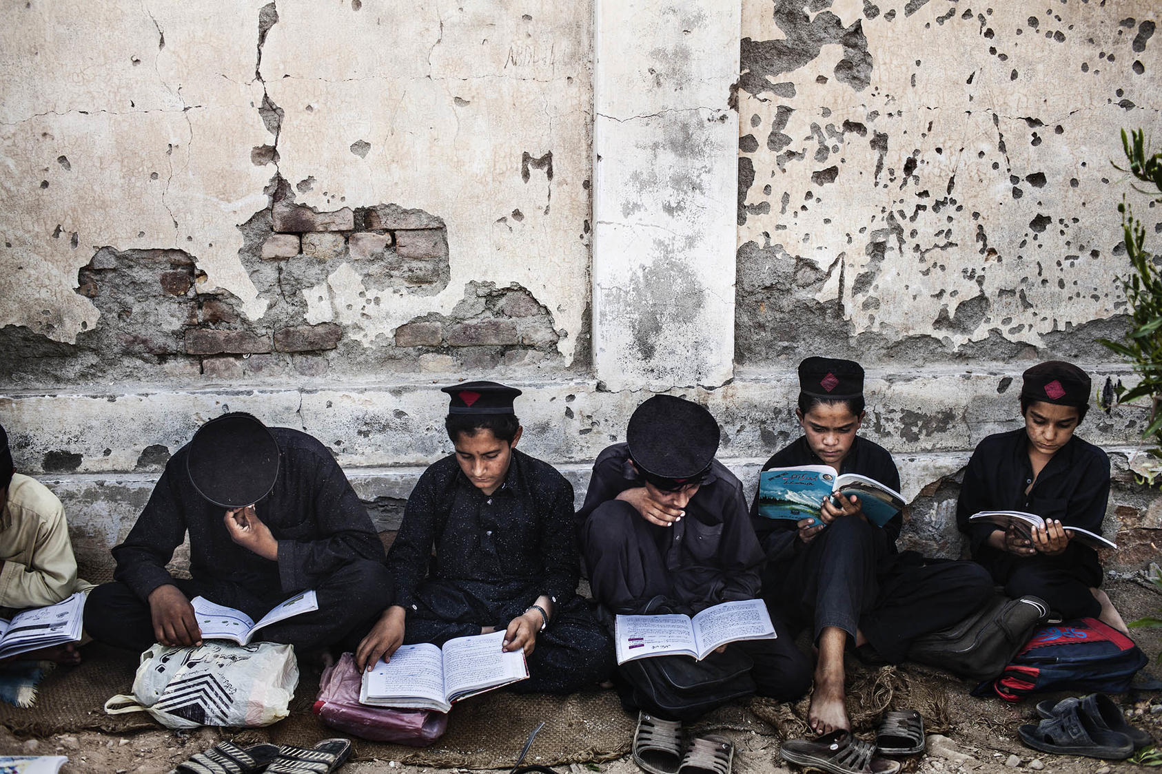 Students study outside of the Government Middle School for Boys, which was bombed by Taliban militants, in the Mohmand Agency in Pakistan, June 10, 2013. (Diego Ibarra Sanchez/The New York Times)