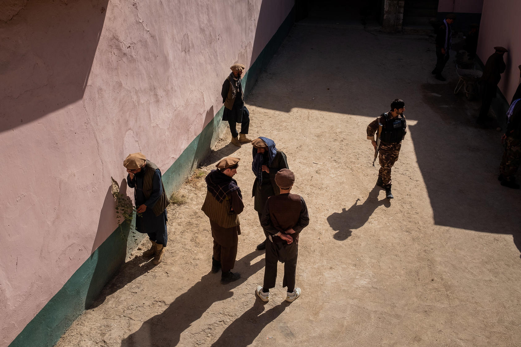 A soldier walks among a group of alleged Taliban fighters at a National Directorate of Security facility in Faizabad in September 2019. The status of prisoners will be a critical issue in future negotiations with the Taliban. (Jim Huylebroek/New York Times)