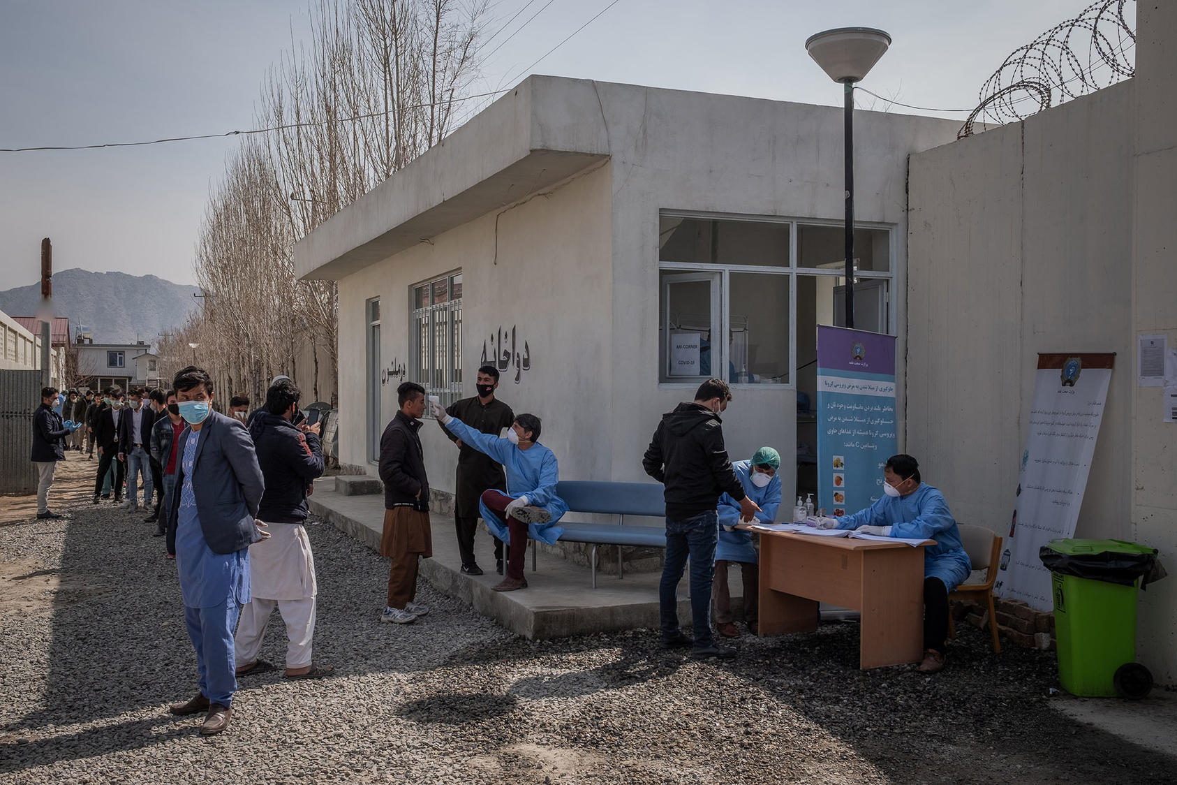 Men, most of whom had returned from Iran and were advised to self-isolate, are screened for the coronavirus outside a hospital in Kabul, Afghanistan, March 17, 2020. (Jim Huylebroek/The New York Times)
