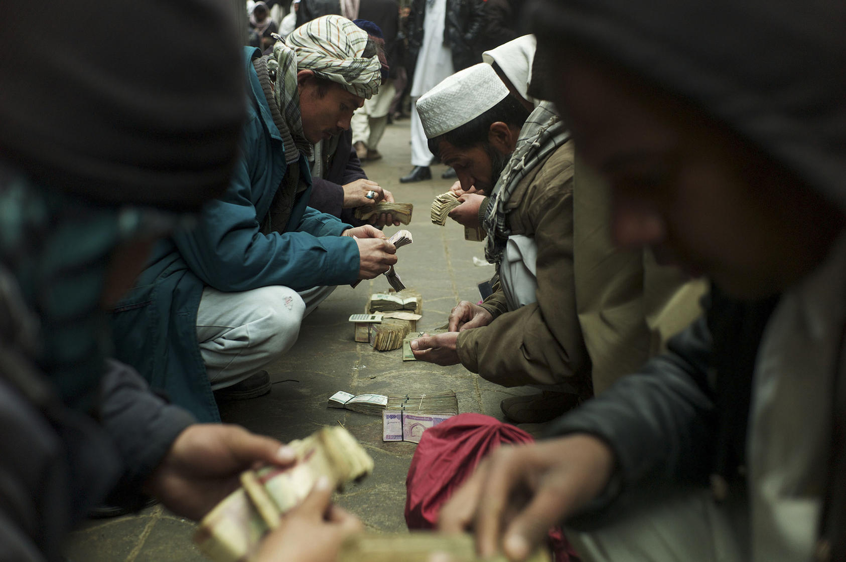 Men negotiate money exchanges at a market in Kabul, on Jan. 29, 2011. (Michael Kamber/The New York Times)