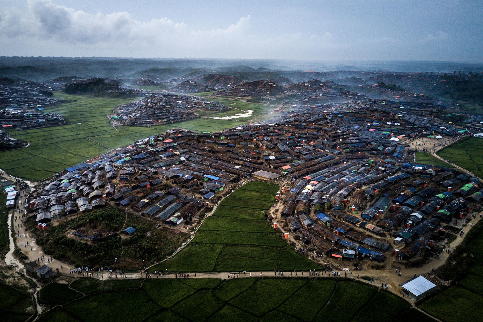Shacks for Rohingya refugees jam hillsides above often flooded rice fields in Bangladesh. Extreme population densities and limited water supplies for many refugees impede basic steps to limit the spread of COVID-19. (Sergey Ponomarev/The New York Times)