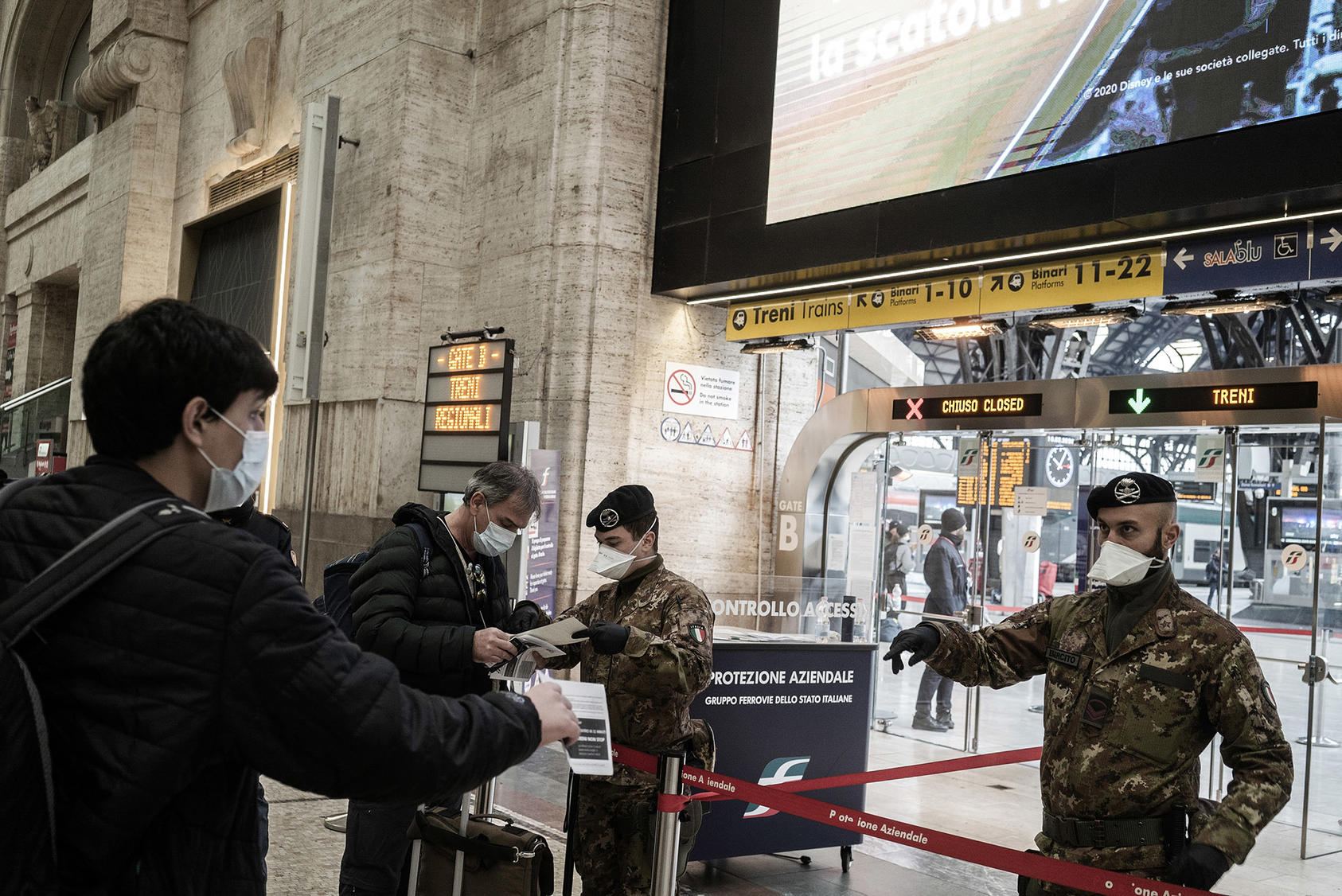 Security forces check passengers at the train station in Milan, March 10, 2020. (Alessandro Grassani/The New York Times)