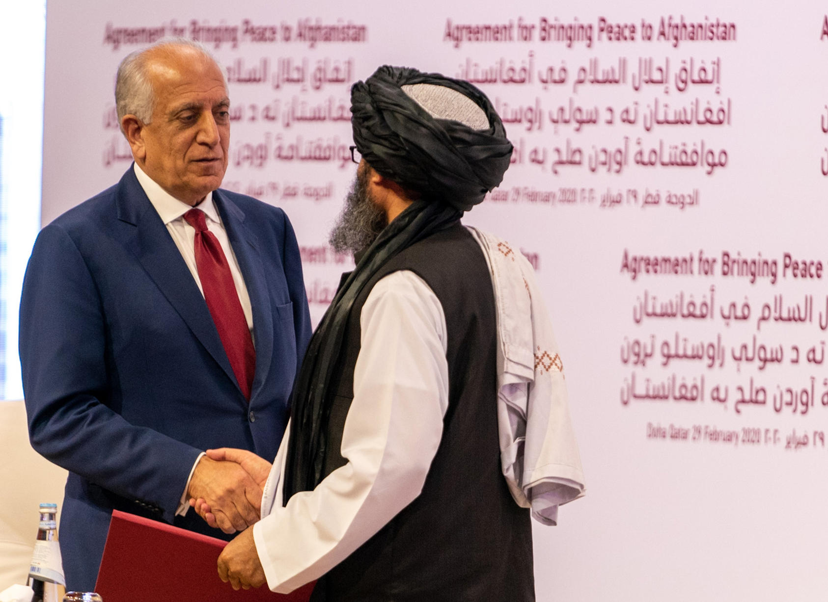 U.S. envoy Zalmay Khalilzad and Taliban negotiator Abdul Ghani Baradar speak after signing the February accord that is meant to be followed by intra-Afghan negotiations for a political settlement to end 40 years of war. (Ron Przysucha/State Department)
