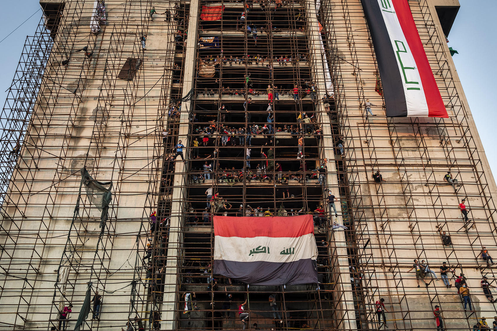 Young men climb scaffolding to reach the upper levels of an unfinished building overlooking mass protests in Tahrir Square in Baghdad, Nov. 1, 2019. (Ivor Prickett/The New York Times)