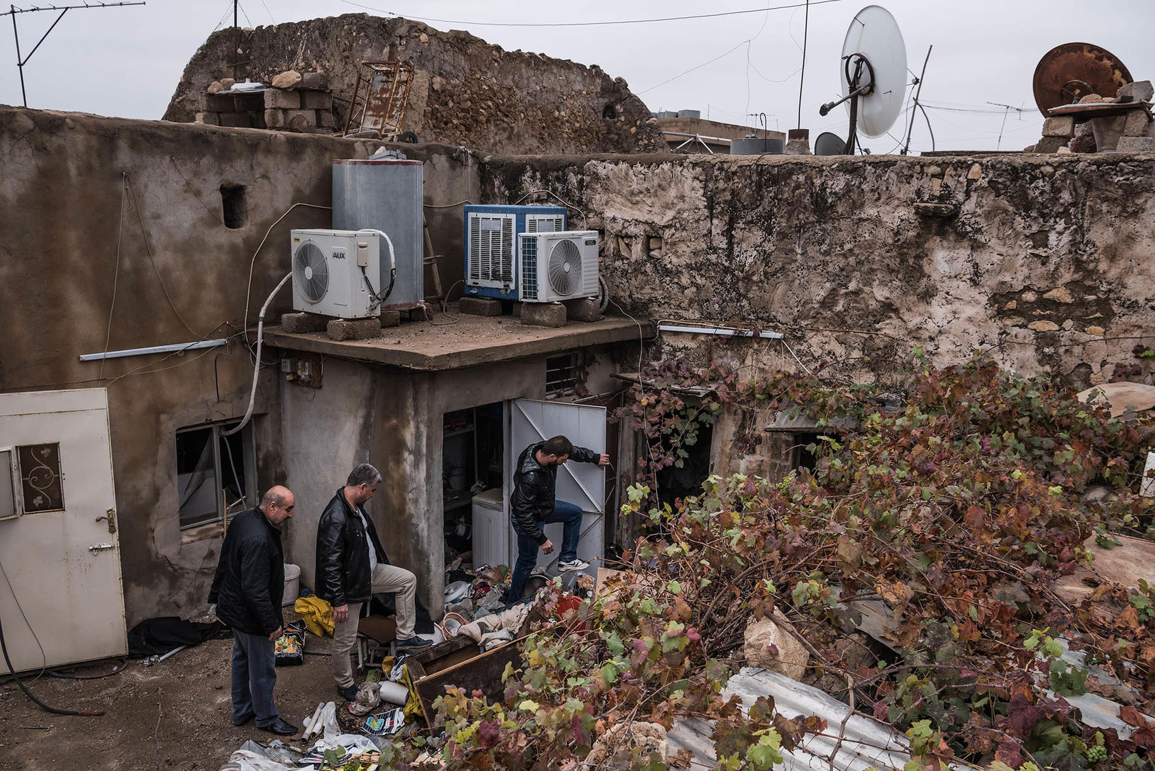 Men from the Al-Saka family check their house after they said they had not been there for two years during Islamic State occupation, in Bartella, a predominantly Christian town in Iraq, Dec. 1, 2016. (Sergey Ponomarev/The New York Times)
