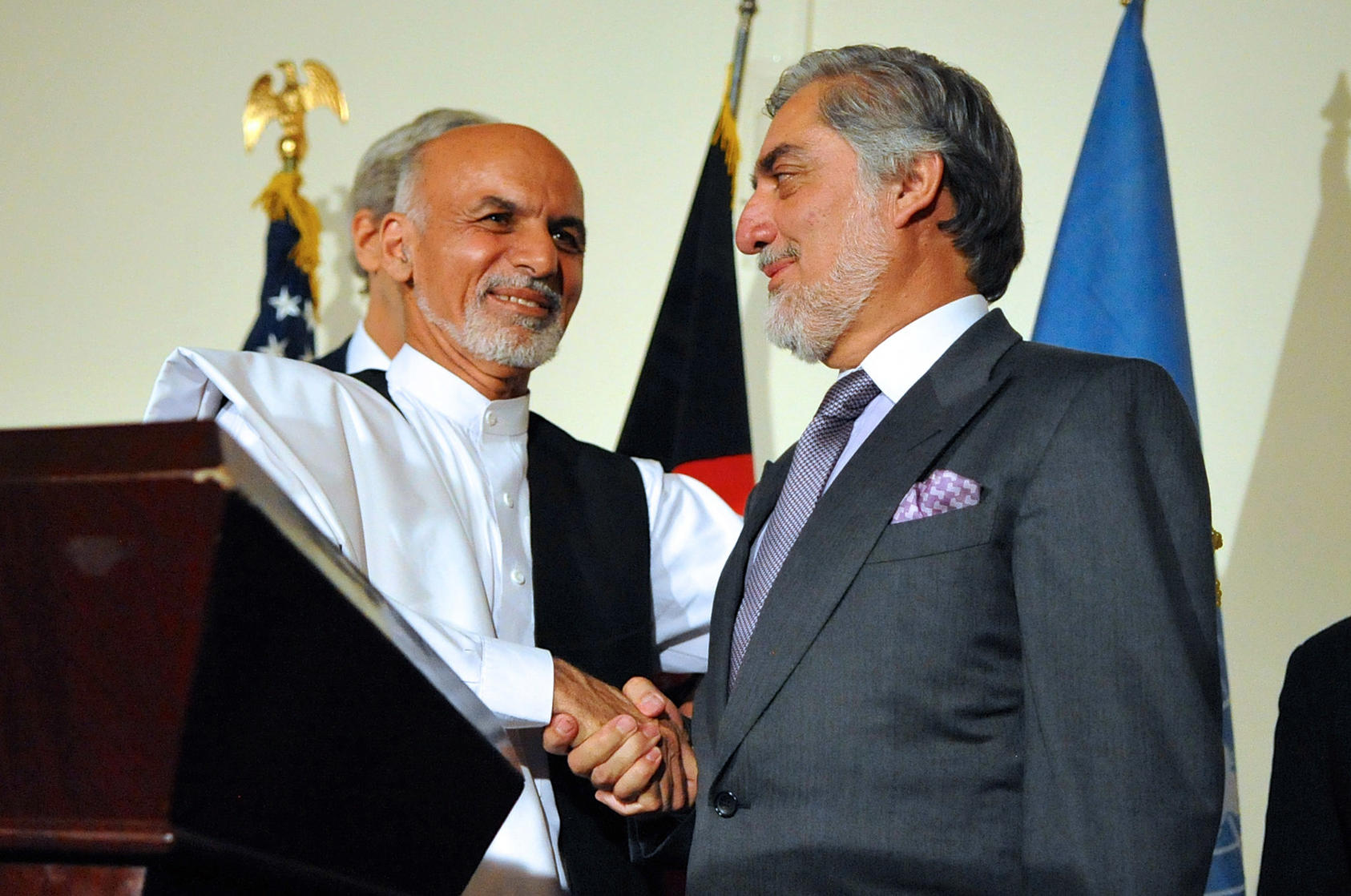 Ashraf Ghani shakes hands with rival Abdullah Abdullah after both addressed reporters at in Kabul on July 12, 2014 about the details of the U.S.-brokered National Unity Government agreement. (U.S. Department of State)