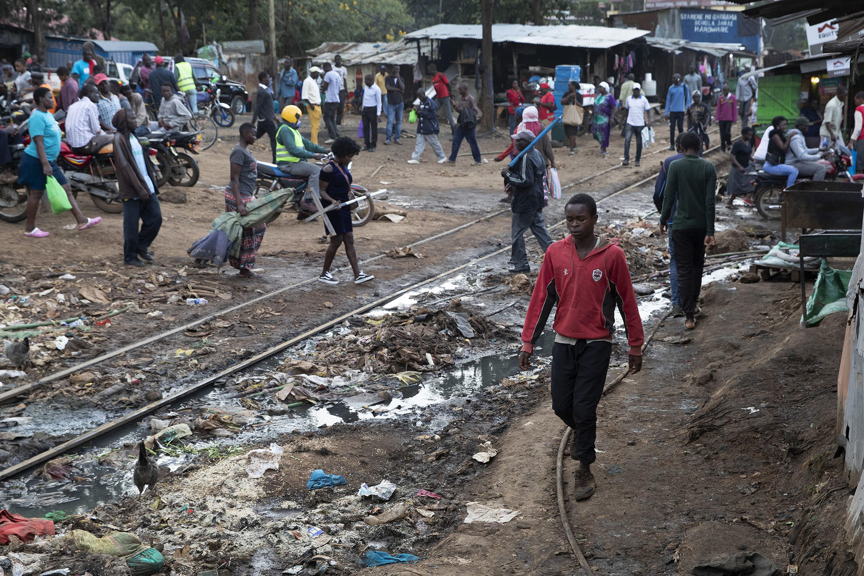 People walk through Kibera, the largest urban slum in Africa, in Nairobi, Kenya, April 7, 2020. (Tyler Hicks/The New York Times)