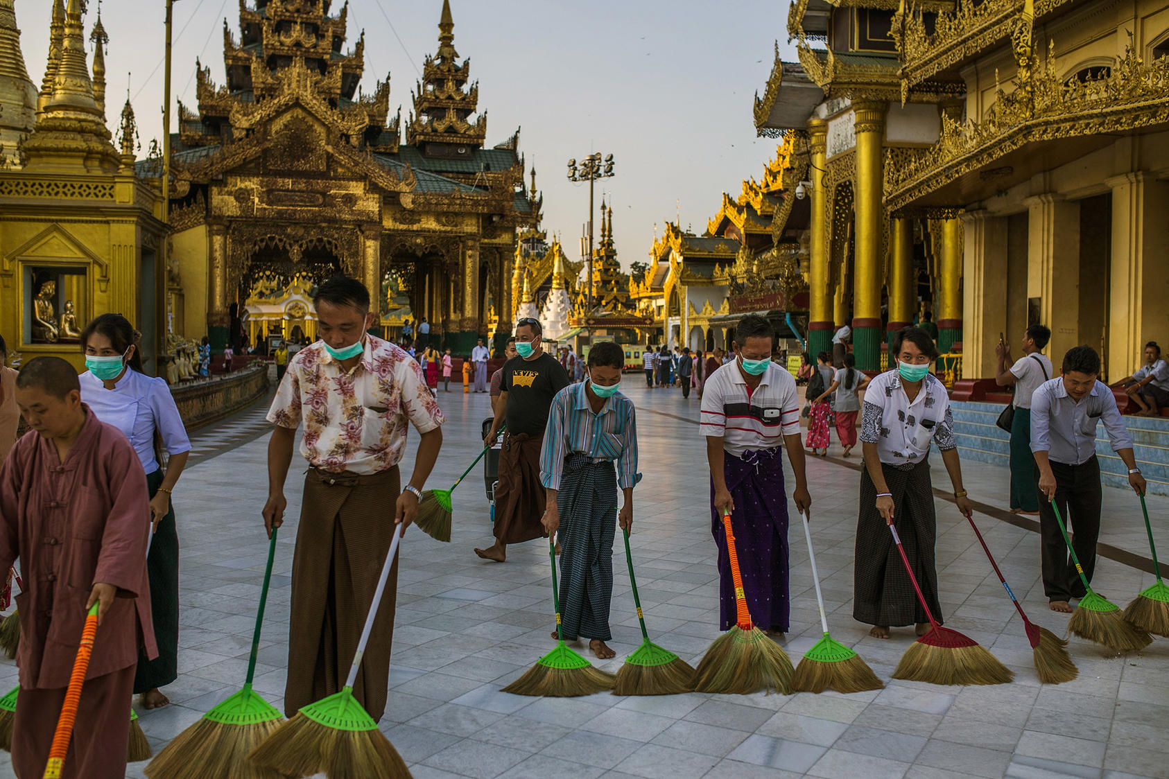 Volunteers, many wearing masks to avoid spreading the COVID19 virus, sweep walkways at the Shwedagon Pagoda, a Buddhist holy site in Yangon, Myanmar, in March. The virus' spread has since led to the pagoda's closure. (Minzayar Oo/The New York Times)