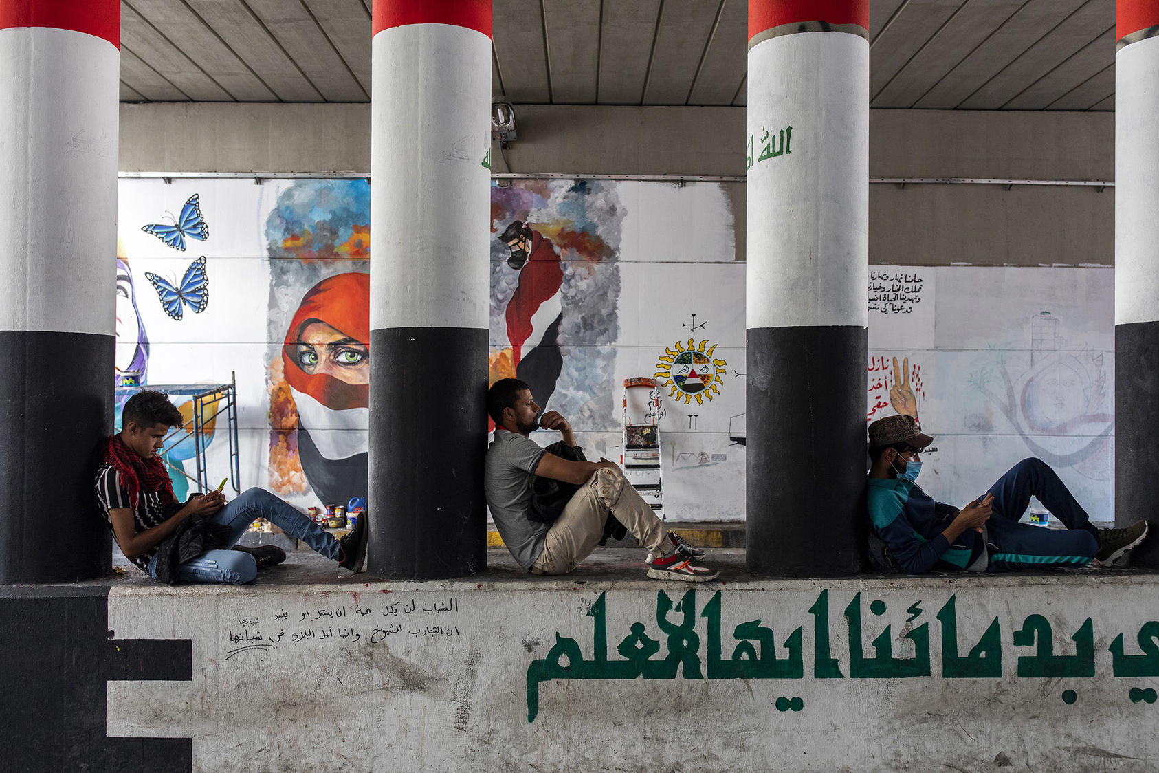 Antigovernment protesters sit in front of murals in Baghdad on Nov. 22, 2019.  (Ivor Prickett/The New York Times)