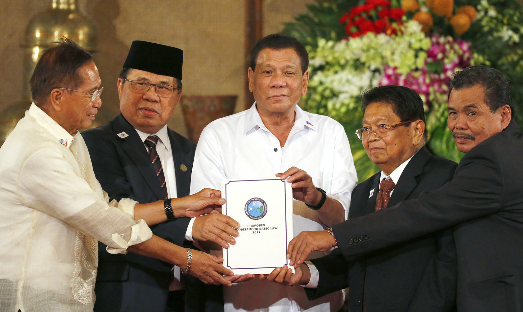 Philippine President Rodrigo Duterte, center, holds the draft of the Bangsamoro Basic Law during a ceremony at Malacañang Palace on July 17, 2017. (Bullit Marquez/AP)