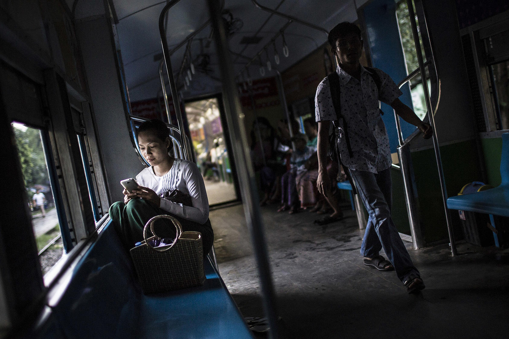 A woman uses her cell phone on the Circle Line train in Yangon, Myanmar, June 2014. (Mathieu Willcocks/The New York Times)