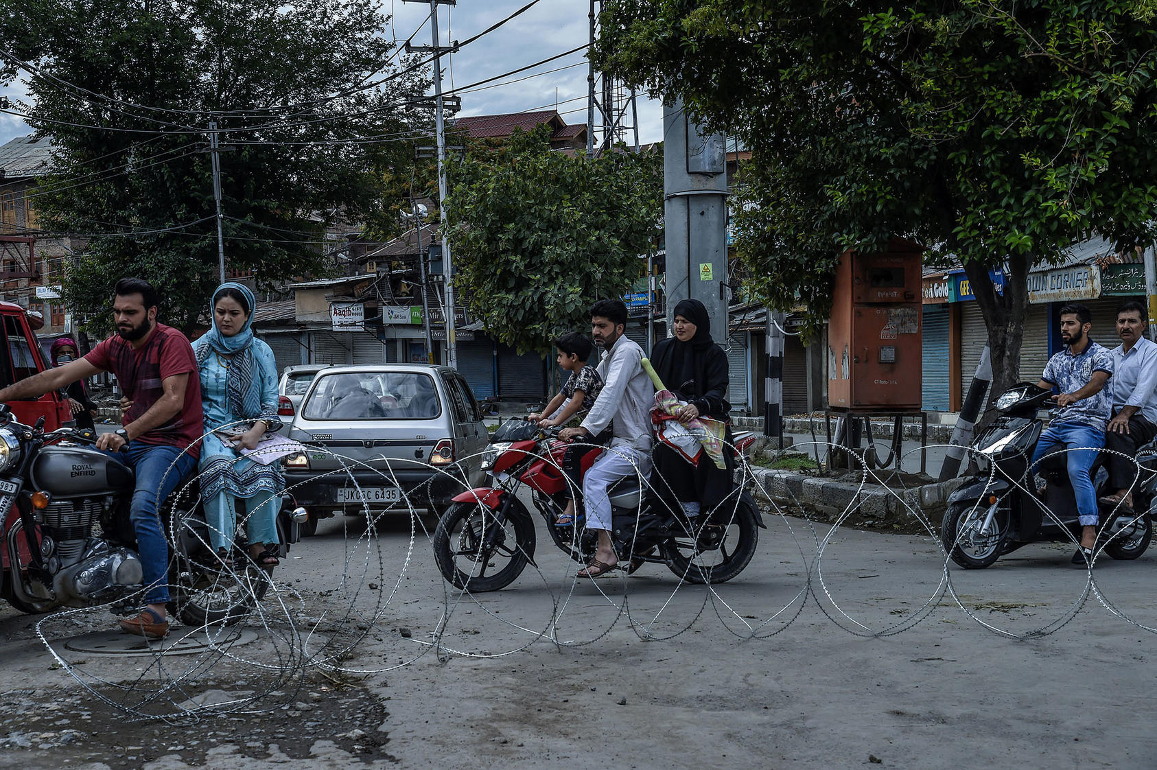 Motorcyclists navigate past barbed-wire placed by Indian security forces in the Kashmiri city of Srinagar on August 10, 2019. (Atul Loke/New York Times)