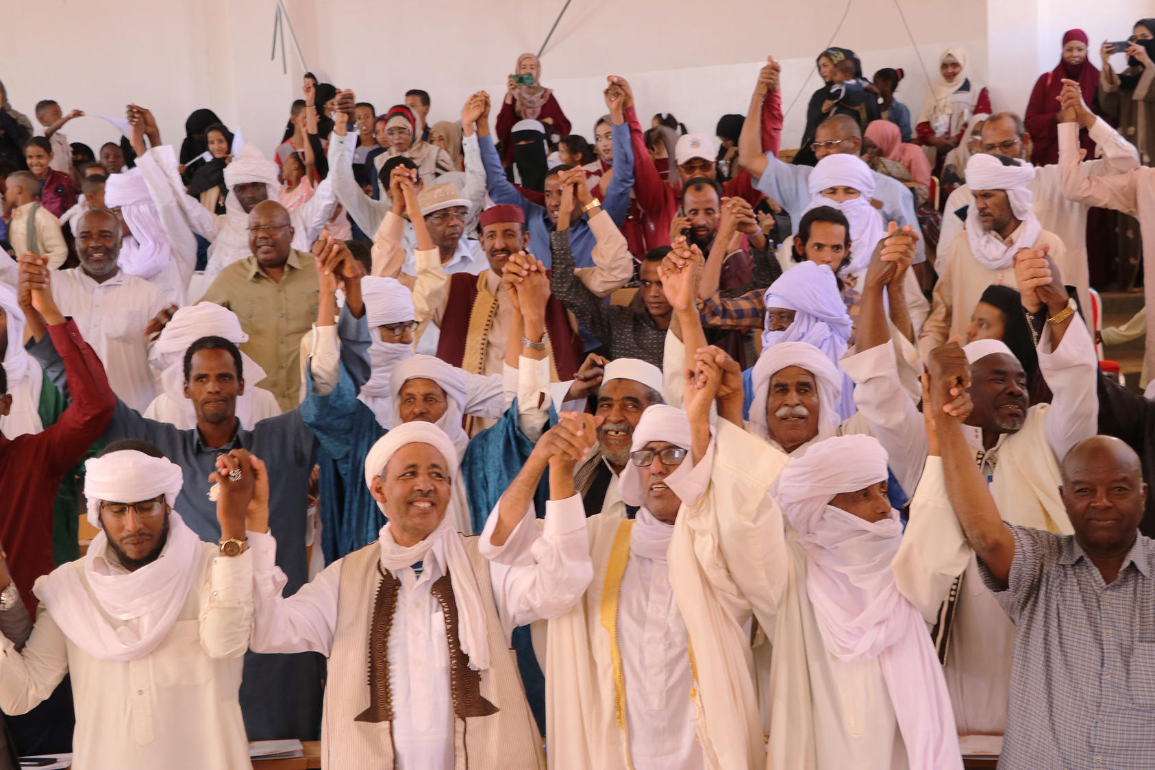 After signing a social pact against school violence, residents of the southern Libyan city of Ubari join hands during a USIP-sponsored Peace Day Celebration in September 2019.
